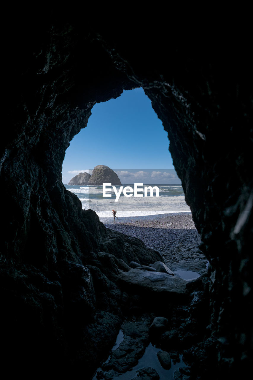 Person At Beach Against Sky Seen Through Cave