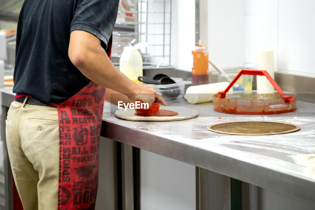 real people, one person, midsection, standing, indoors, food and drink, food, occupation, preparation, kitchen, domestic room, working, commercial kitchen, preparing food, freshness, table, food and drink establishment, men, kitchen counter, chef