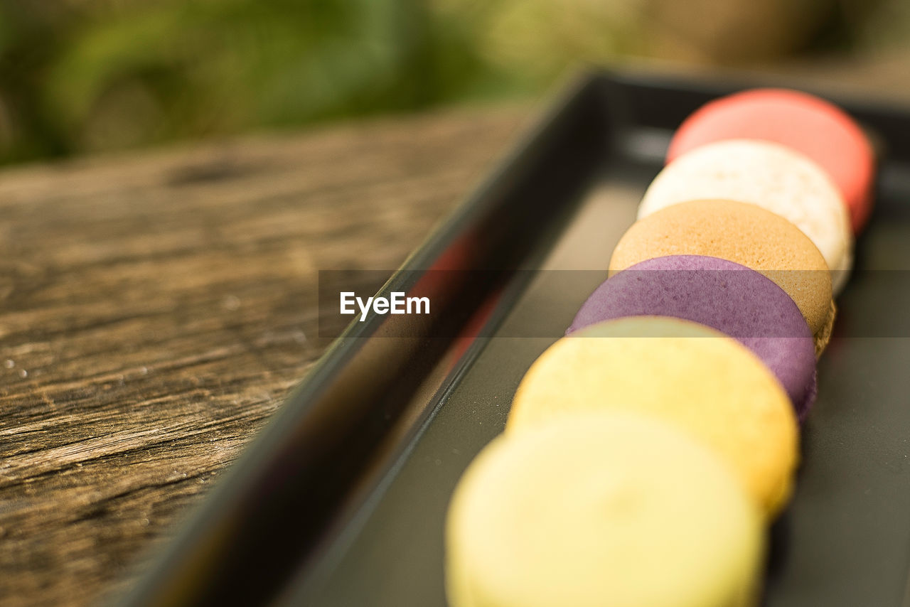 HIGH ANGLE VIEW OF MULTI COLORED PENCILS ON WOODEN TABLE