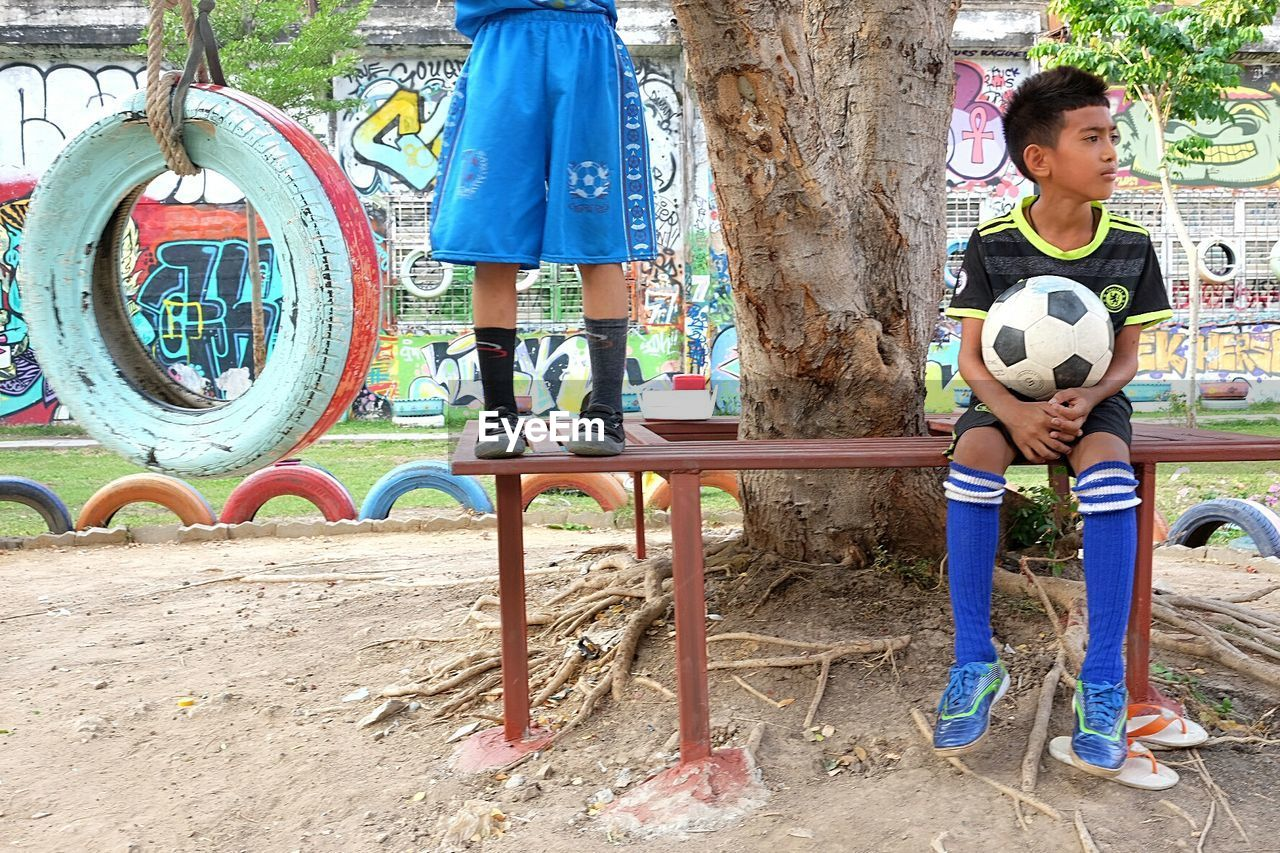 day, lifestyles, leisure activity, playing, sport, real people, outdoors, two people, boys, full length, friendship, togetherness, men, tree, young adult, people