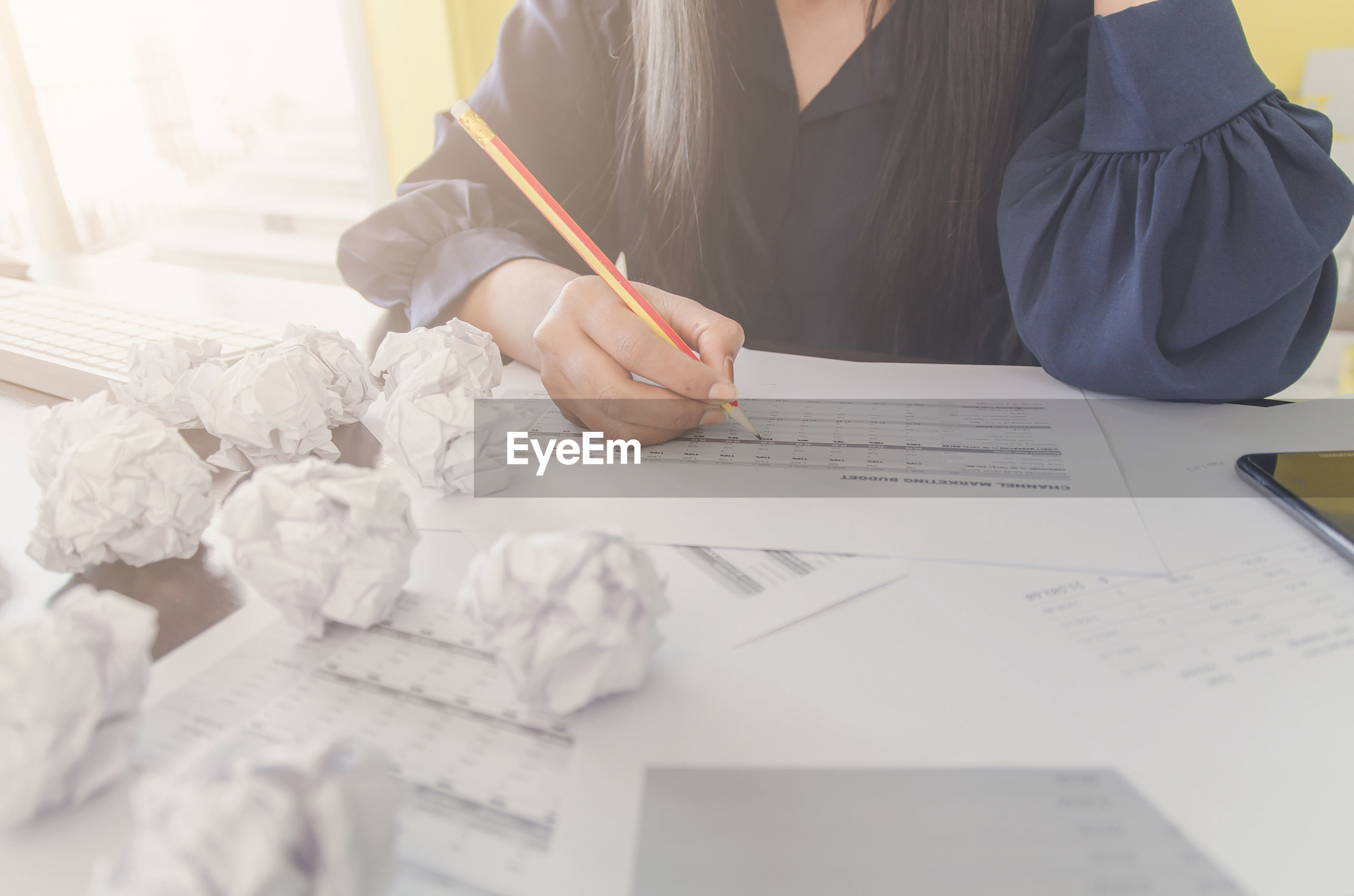 Midsection of businesswoman working with crumpled paper balls on desk