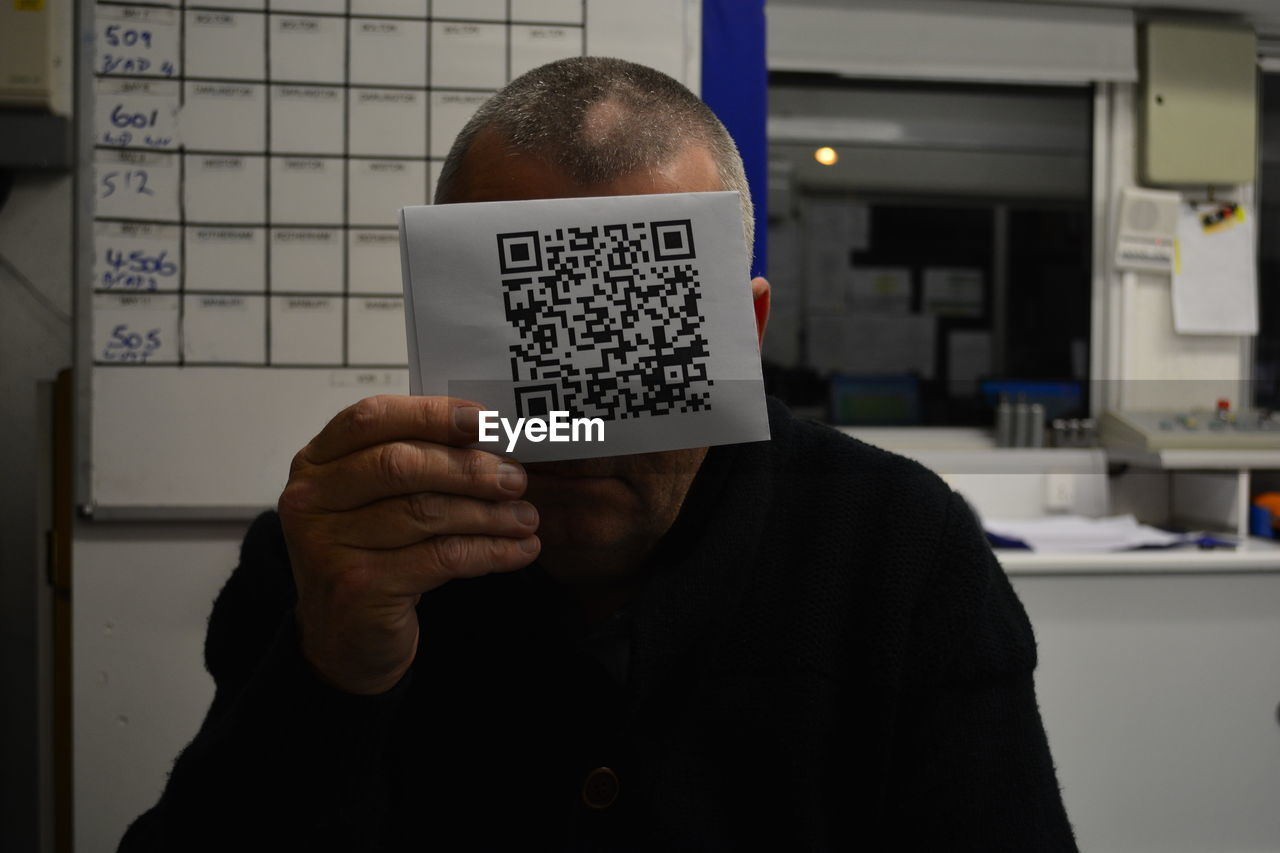 Close-Up Of Man Holding Qr Code At Office