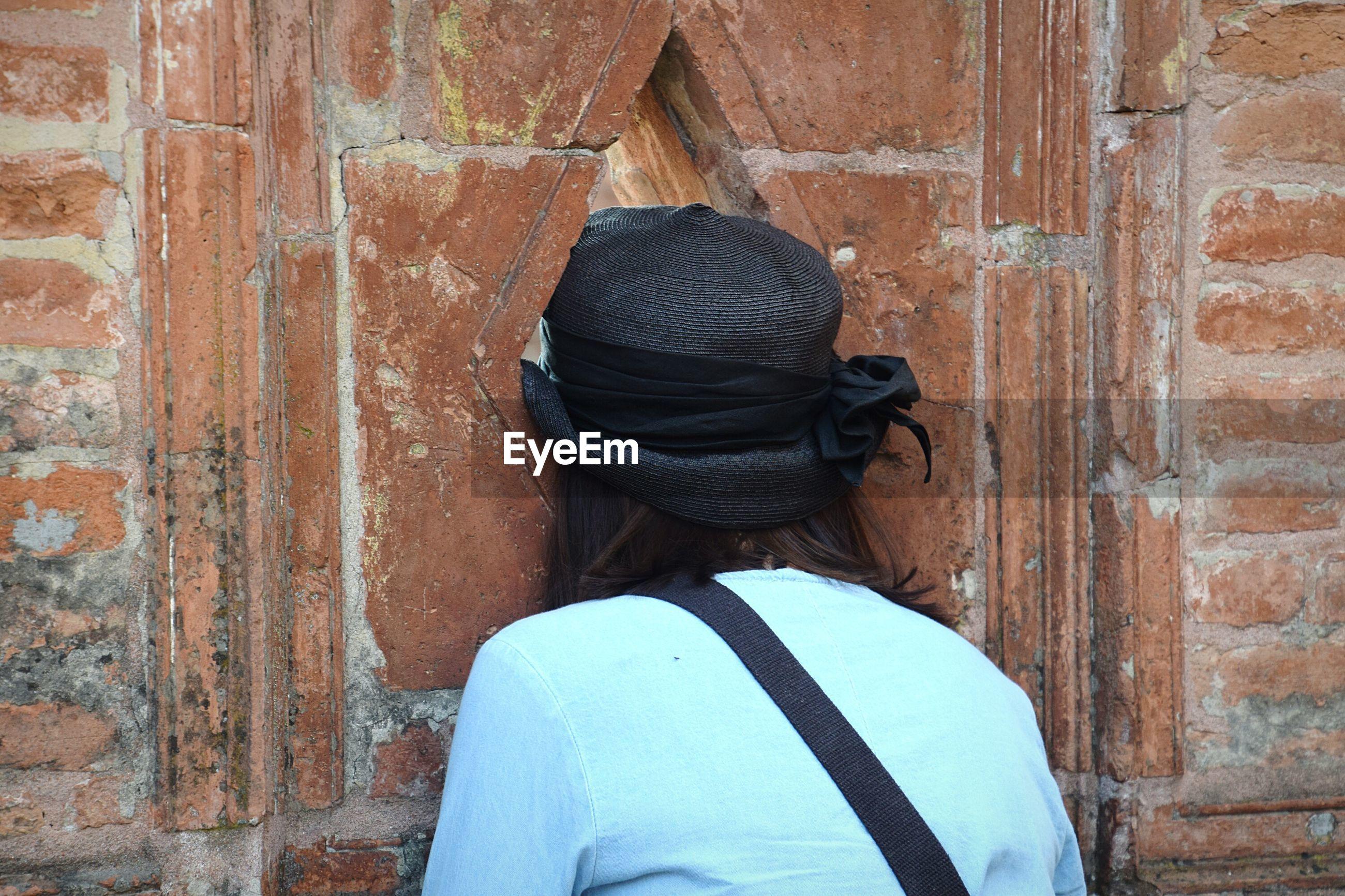 Rear view of woman peeking through hole in wall