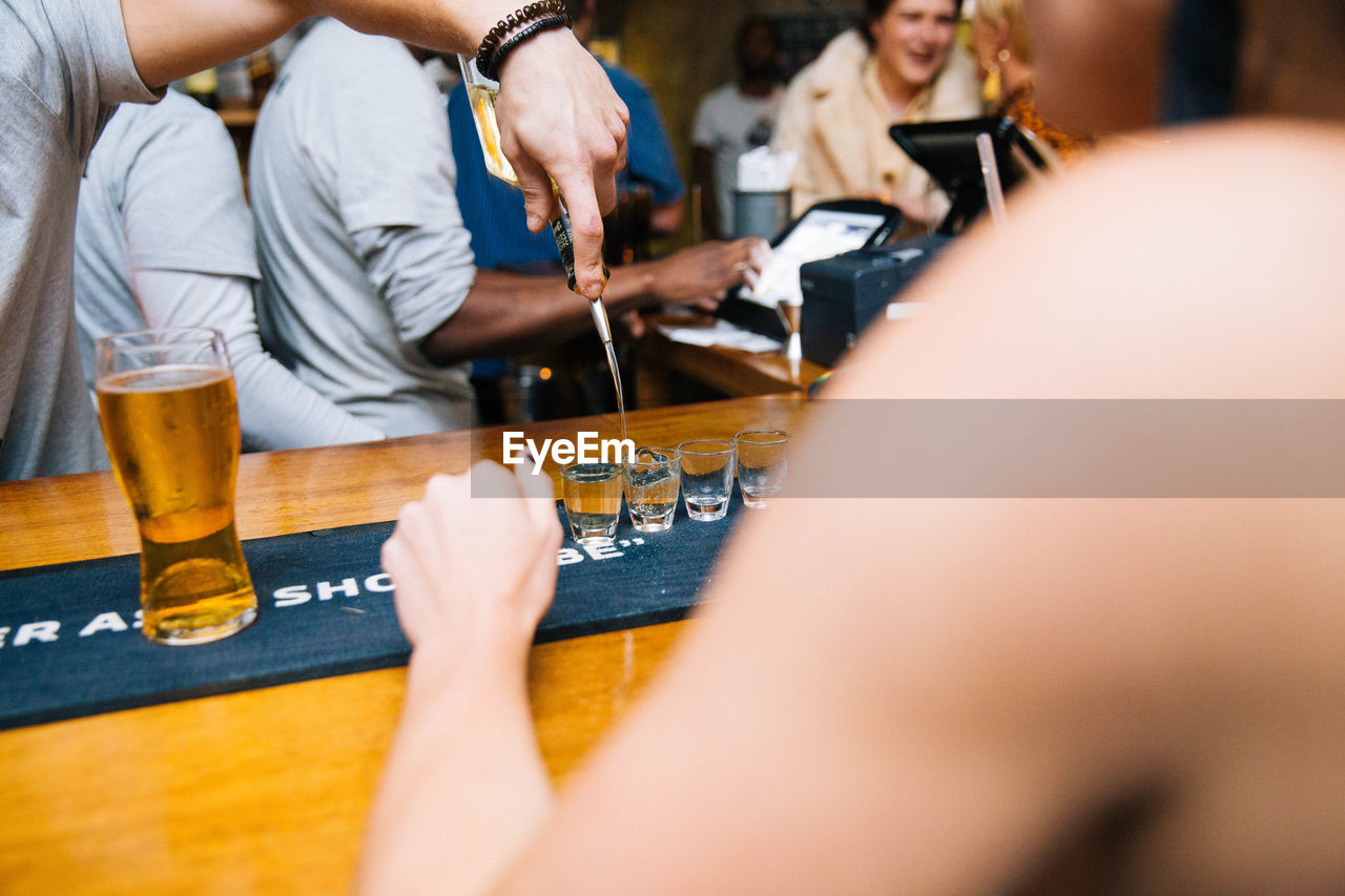 human hand, beer, human body part, selective focus, drink, men, alcohol, group of people, beer - alcohol, hand, midsection, real people, refreshment, people, arts culture and entertainment, adult, women, playing, indoors, holding, glass
