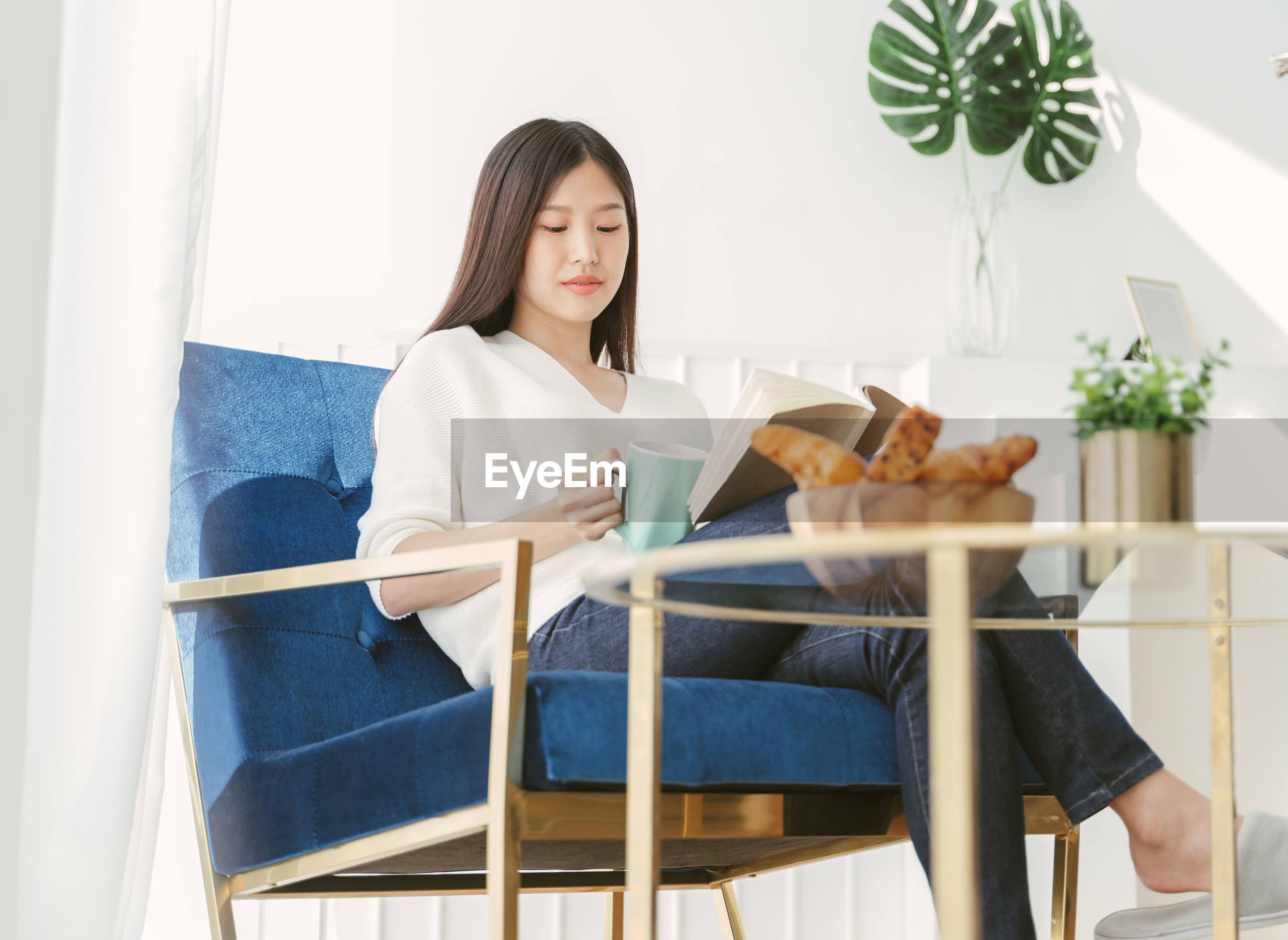 Woman reading book while sitting on chair by bread and coffee cup