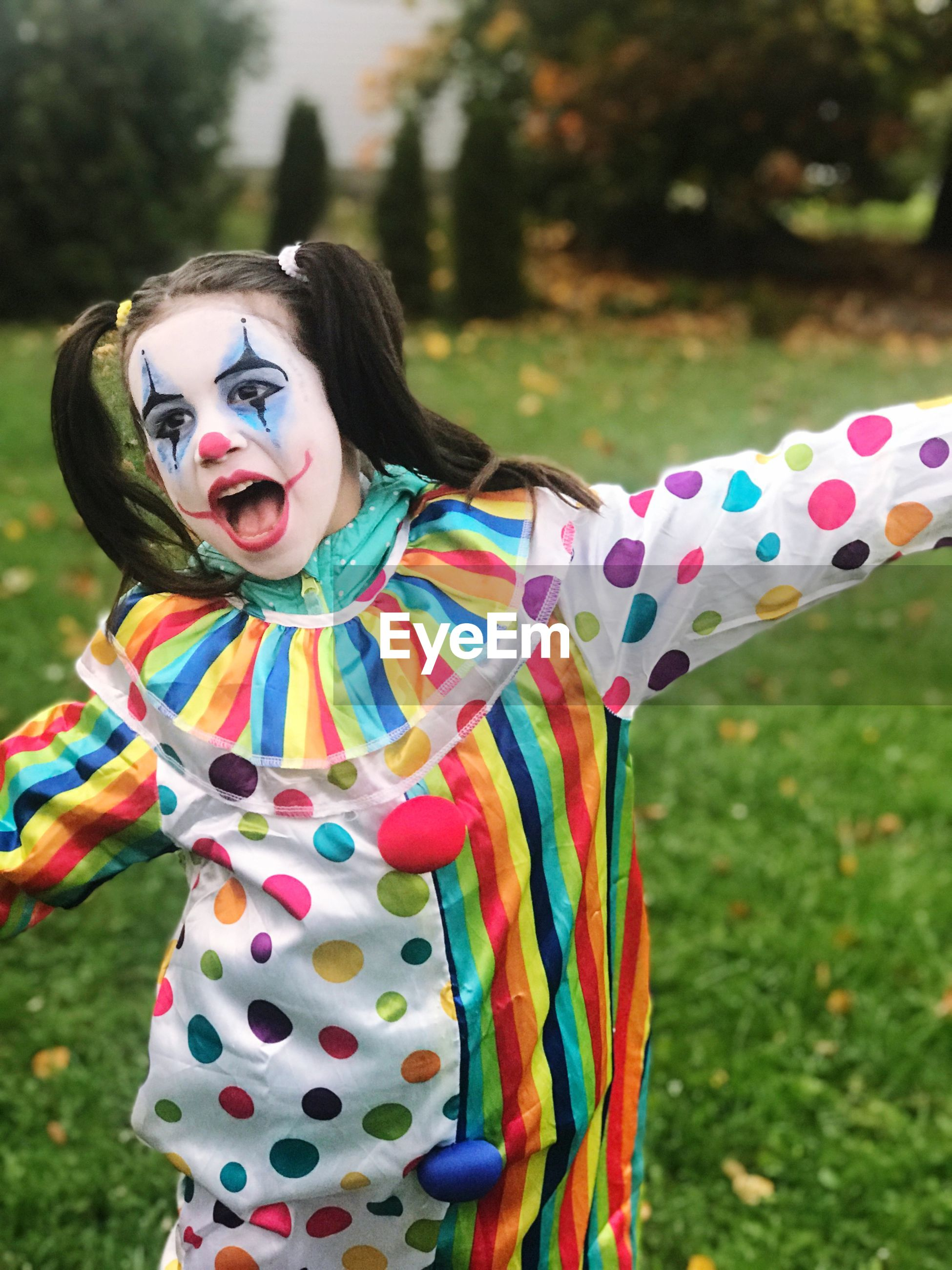 Thoughtful girl wearing clown costume while standing in yard