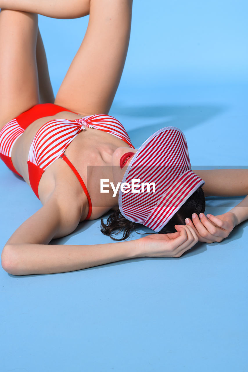 Woman In Bikini Lying Over Blue Background