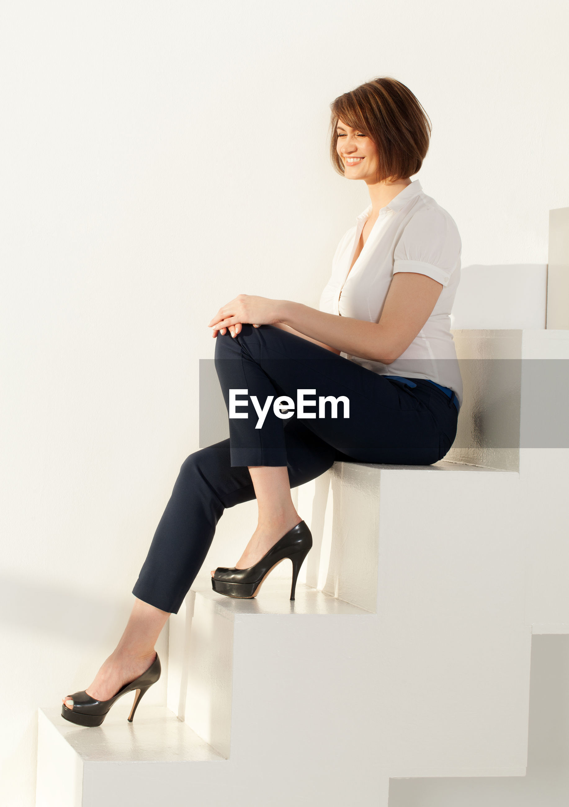 Side view of smiling businesswoman sitting on steps in office