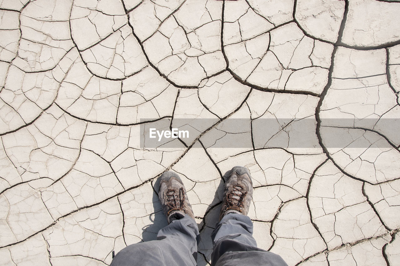 Low Section Of Man Standing On Dried Cracked Soil During Draught