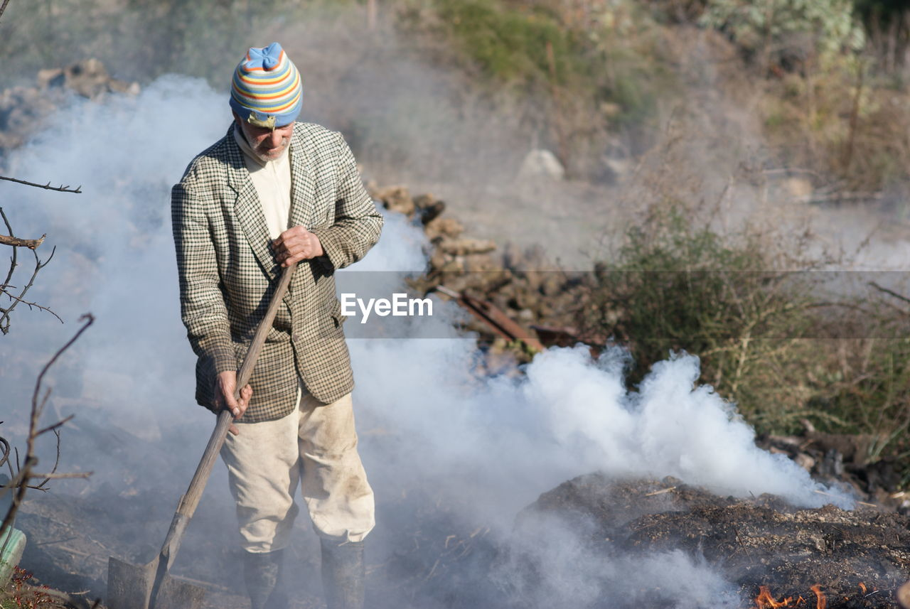 real people, one person, smoke - physical structure, leisure activity, casual clothing, lifestyles, day, standing, outdoors, warm clothing, nature, mountain, water, young adult