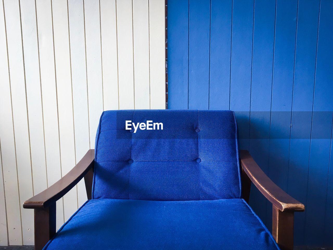 Empty Blue Armchair Against Wall