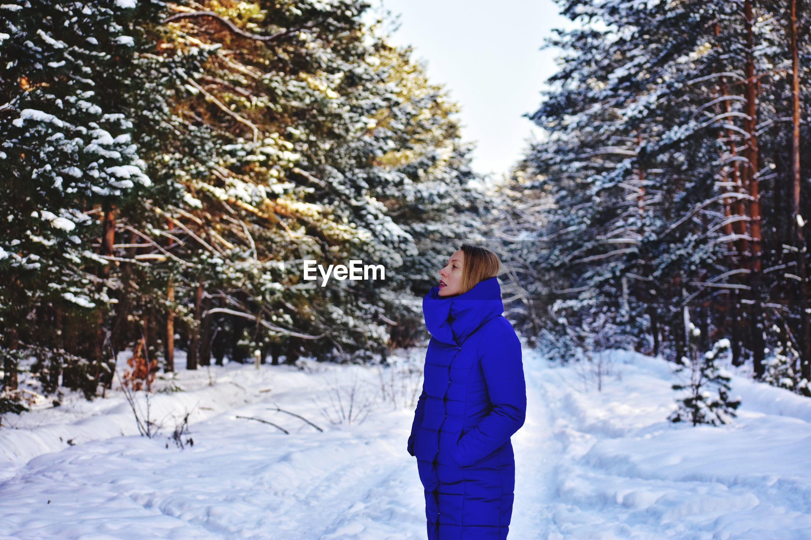Woman looking up while standing on snowy land
