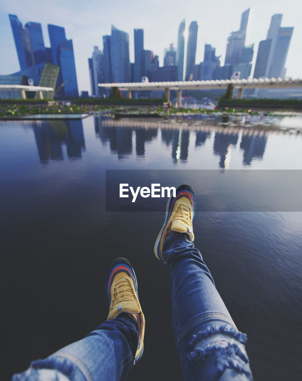 water, low section, built structure, architecture, human leg, building exterior, personal perspective, shoe, nature, human body part, city, day, body part, real people, reflection, one person, outdoors, lake, leisure activity, office building exterior, jeans, human foot, skyscraper, human limb