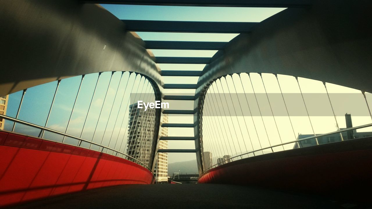 Low angle view of bridge and building in city against sky