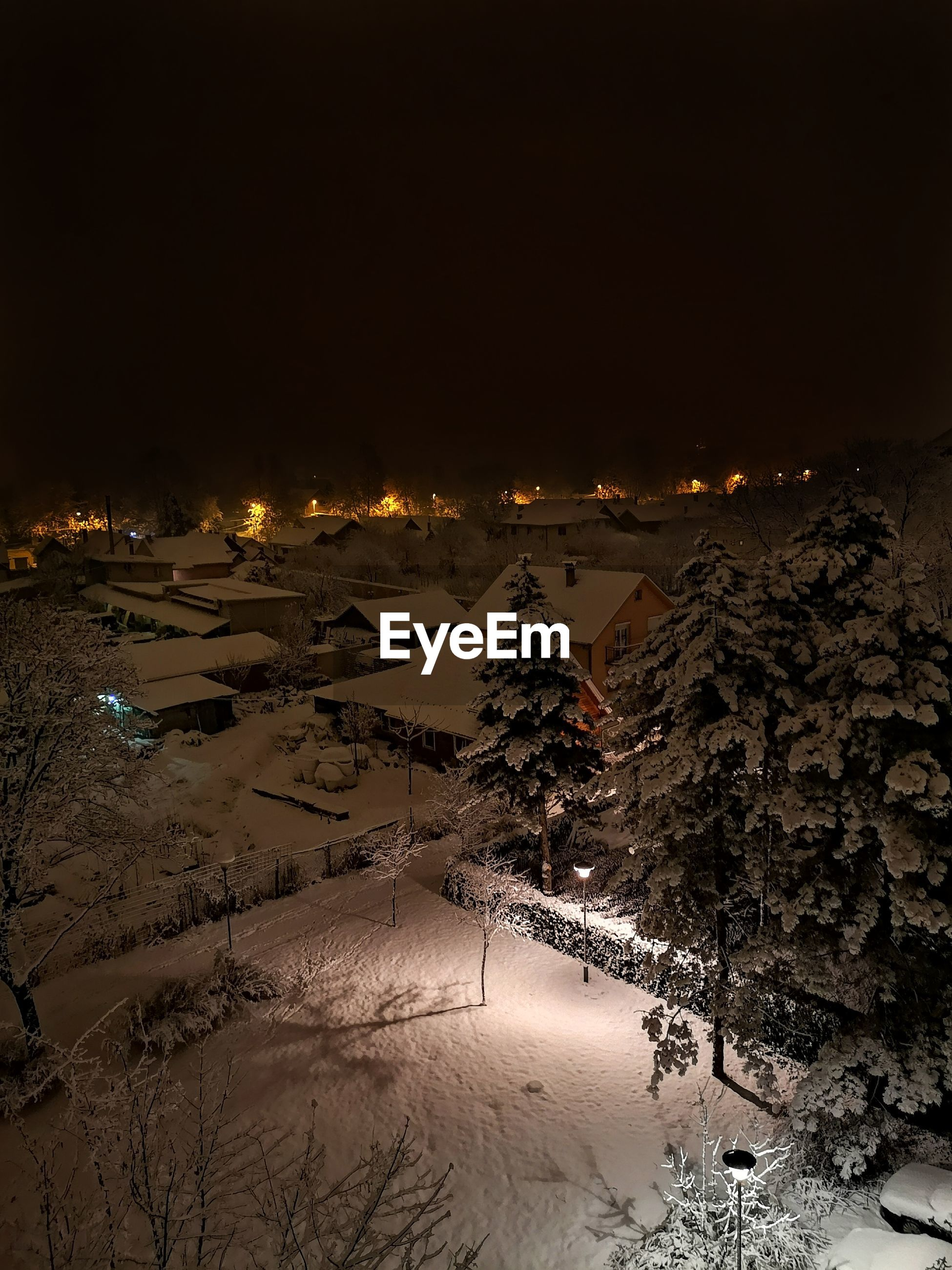 AERIAL VIEW OF ILLUMINATED CITY AGAINST SKY DURING WINTER