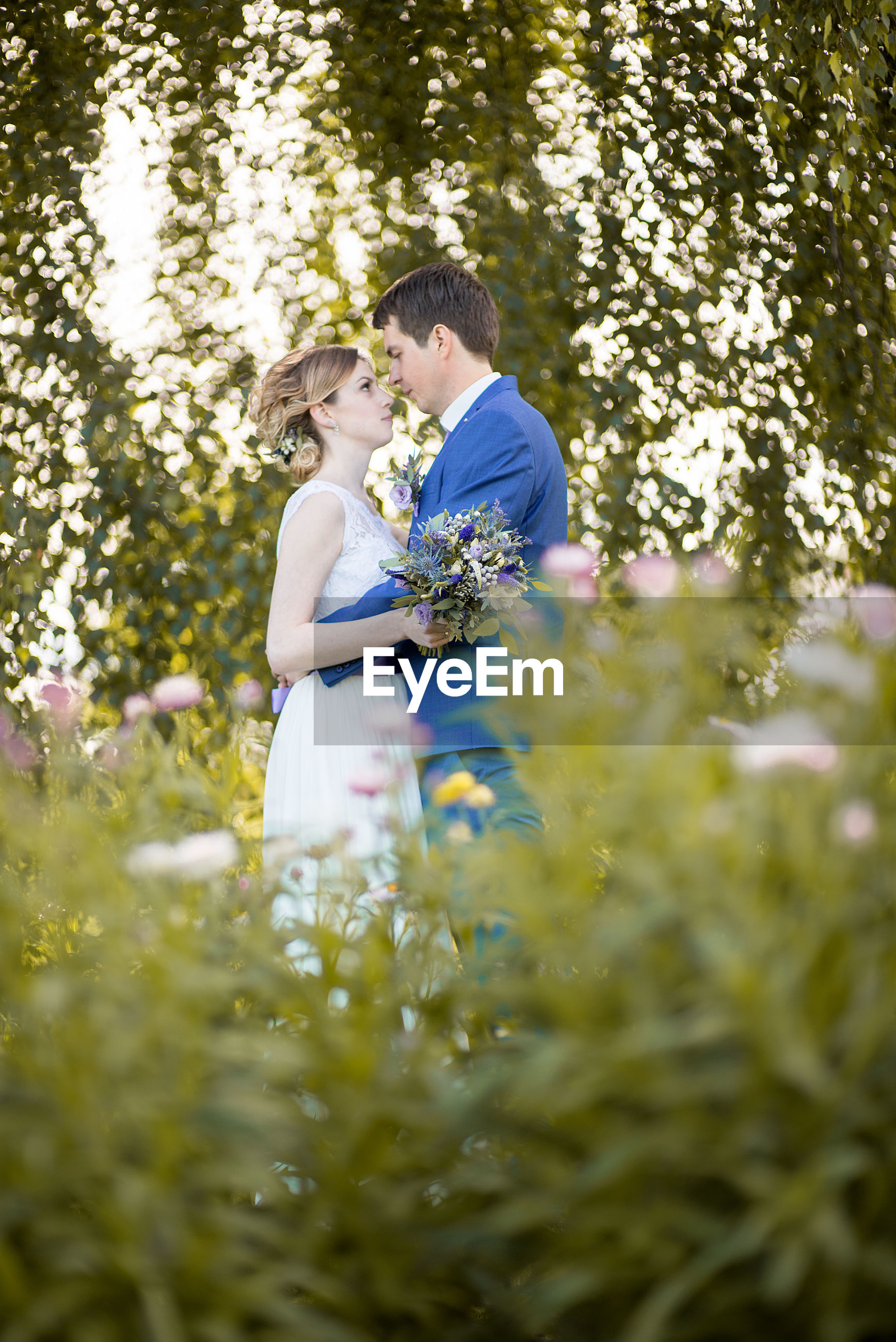 Side view of newlywed couple standing on grassy field at park