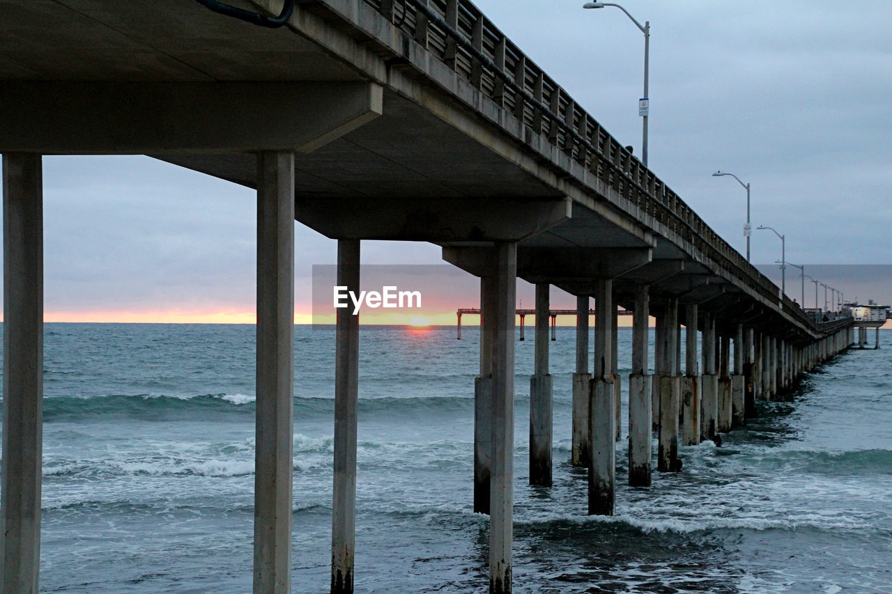 water, sea, sky, architecture, land, beach, built structure, architectural column, sunset, nature, horizon over water, horizon, pier, cloud - sky, bridge, connection, scenics - nature, tranquility, no people, bridge - man made structure, outdoors, underneath
