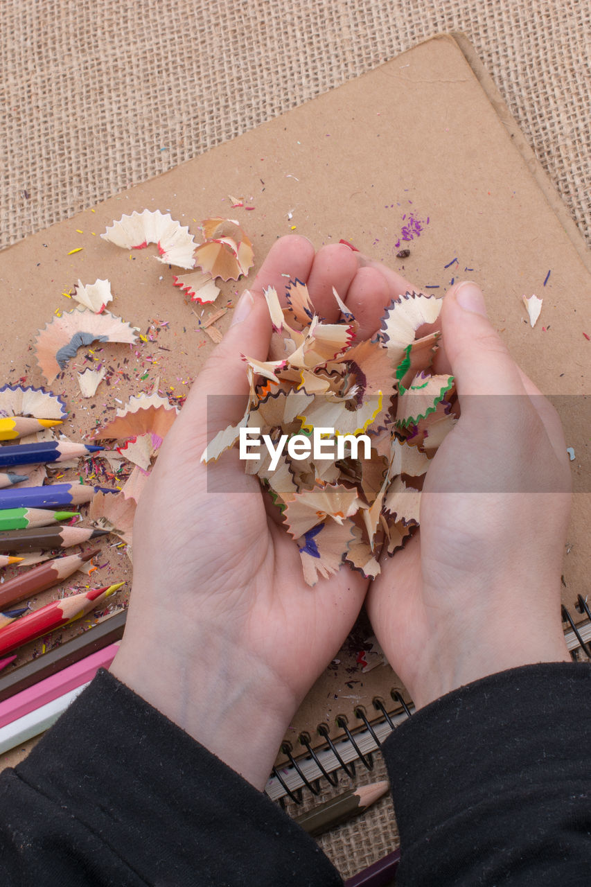 High angle view of person hands holding pencil shavings on table