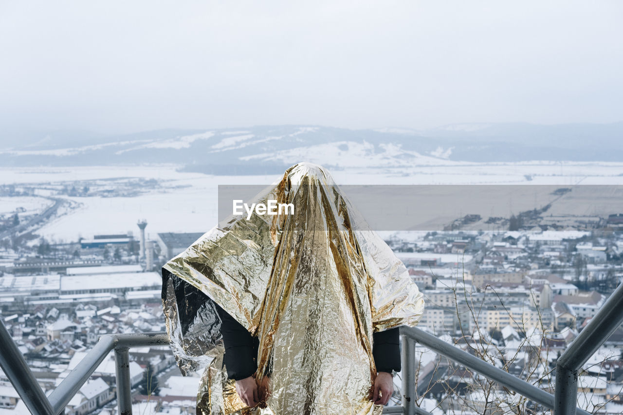 Person Covered In Golden Paper Standing Against Cityscape