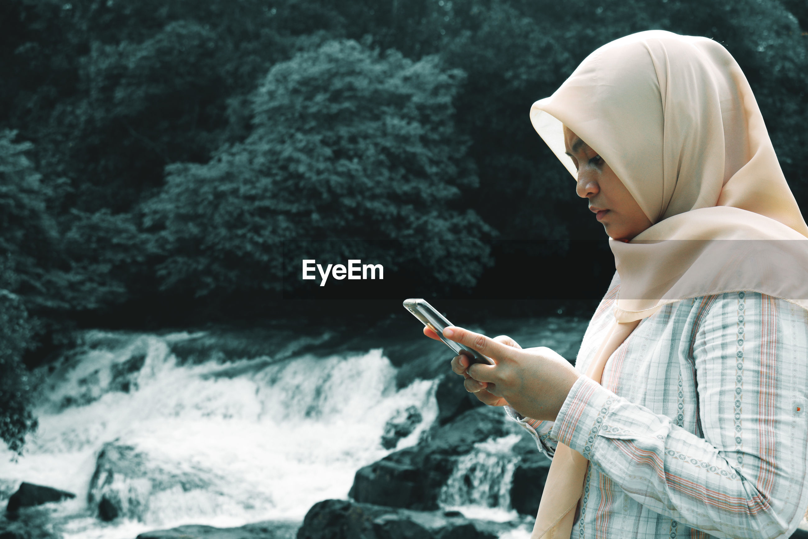 Side view of woman using mobile phone by waterfall in forest