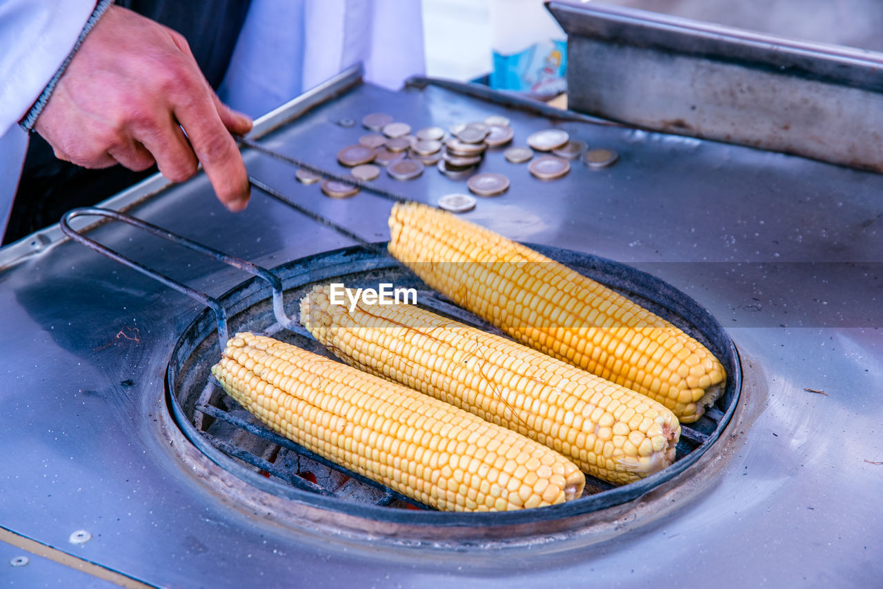 corn, food and drink, food, preparation, real people, sweetcorn, vegetable, freshness, human hand, one person, hand, healthy eating, wellbeing, day, corn on the cob, yellow, close-up, outdoors, heat - temperature, preparing food