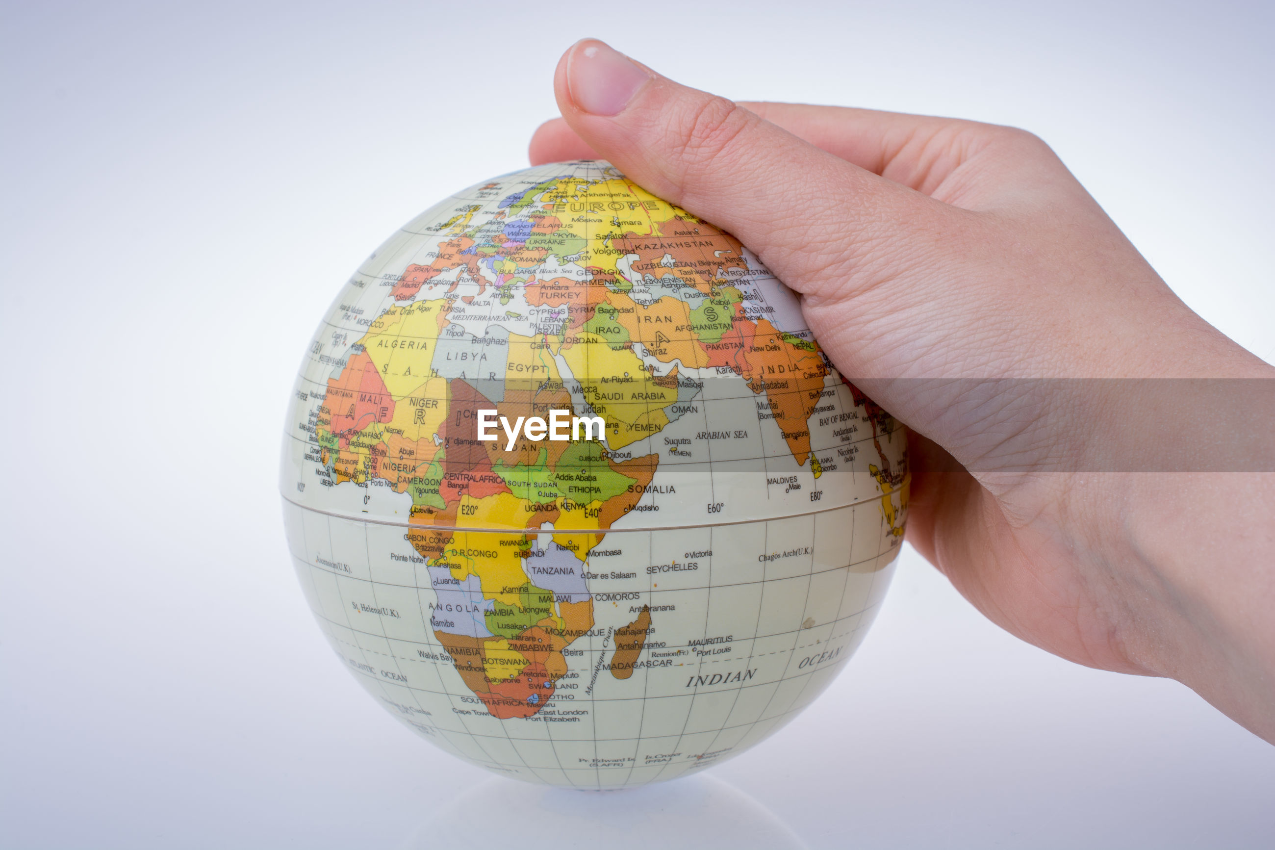 Close-up of woman hand holding globe against white background