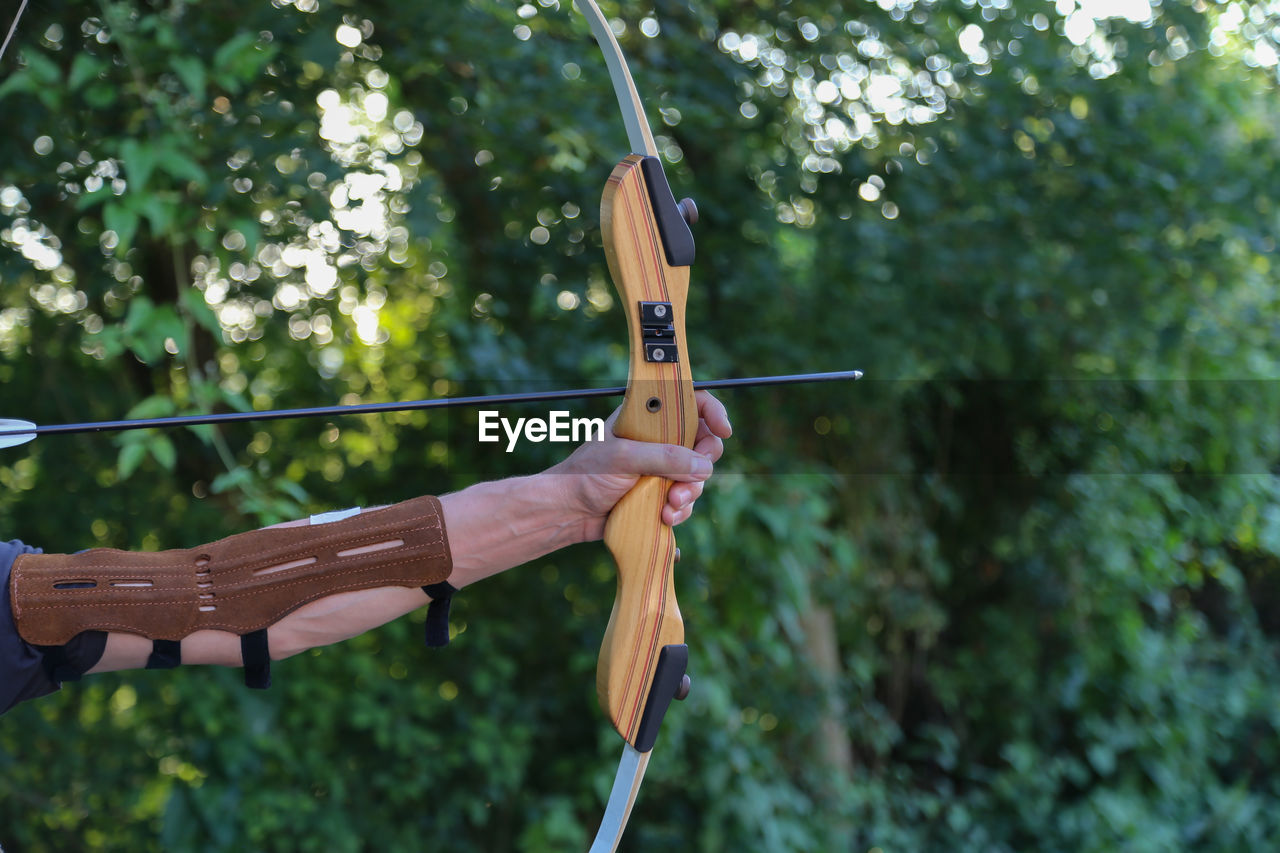 human hand, hand, holding, real people, one person, focus on foreground, plant, human body part, day, lifestyles, leisure activity, nature, unrecognizable person, tree, music, weapon, arrow - bow and arrow, outdoors, arts culture and entertainment