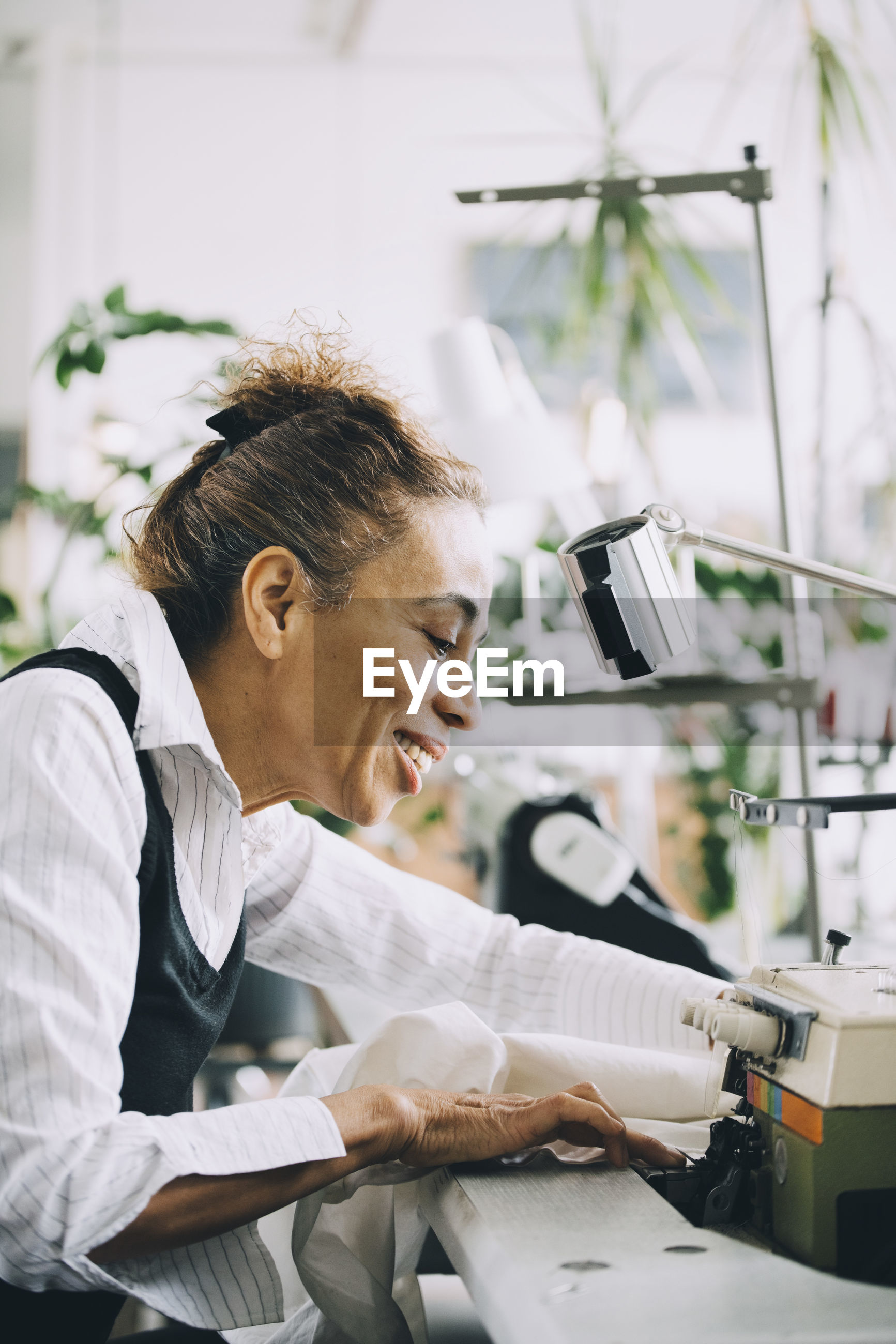 WOMAN LOOKING AT CAMERA IN OFFICE