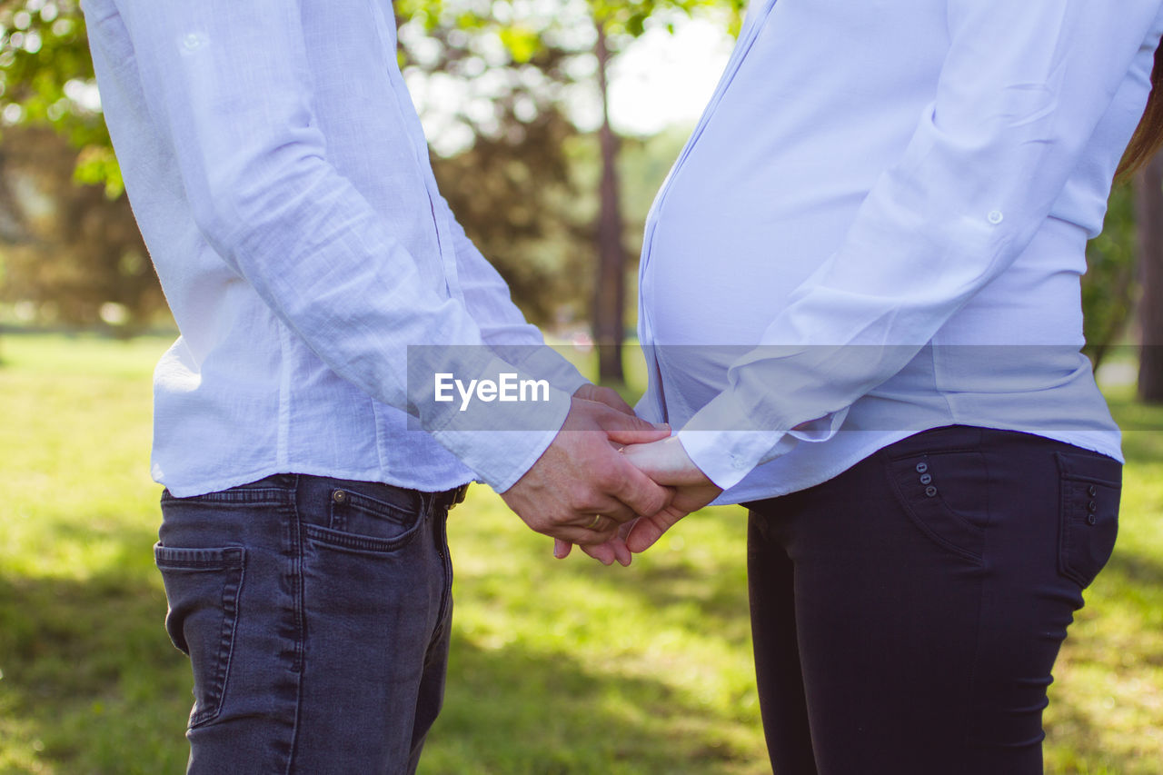 two people, men, love, positive emotion, couple - relationship, holding hands, real people, midsection, togetherness, bonding, adult, heterosexual couple, focus on foreground, hand, human hand, event, married, wedding, day, bridegroom, outdoors, wedding ceremony