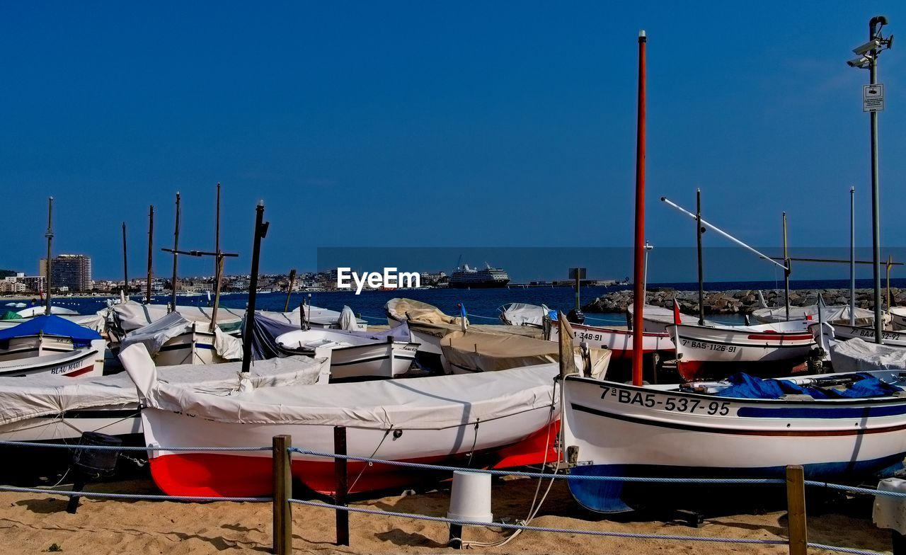 moored, nautical vessel, water, no people, sea, in a row, mode of transport, outdoors, day, transportation, blue, chair, clear sky, wood - material, nature, harbor, sailboat, mast, sky, beauty in nature