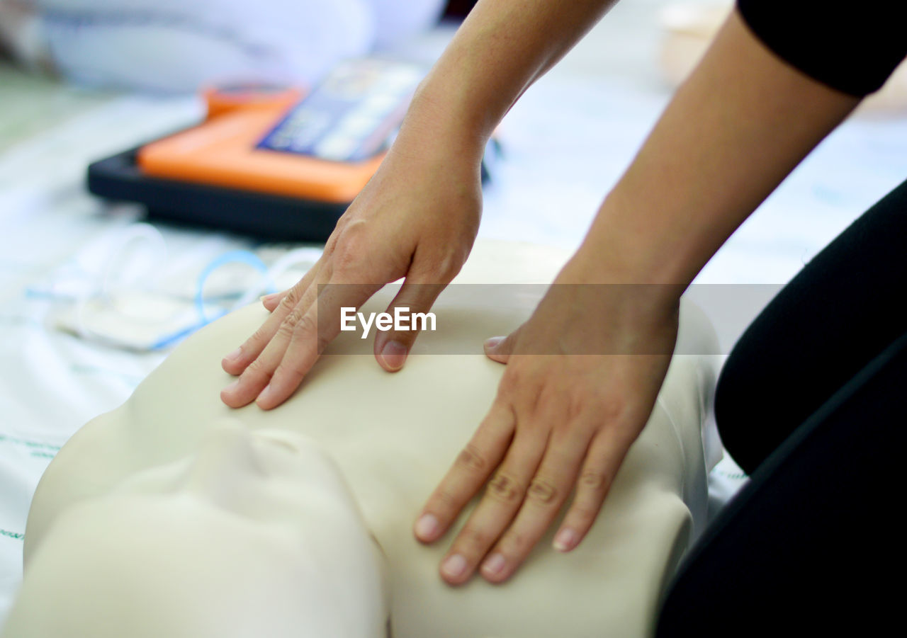 Cropped hands of woman performing cpr on dummy