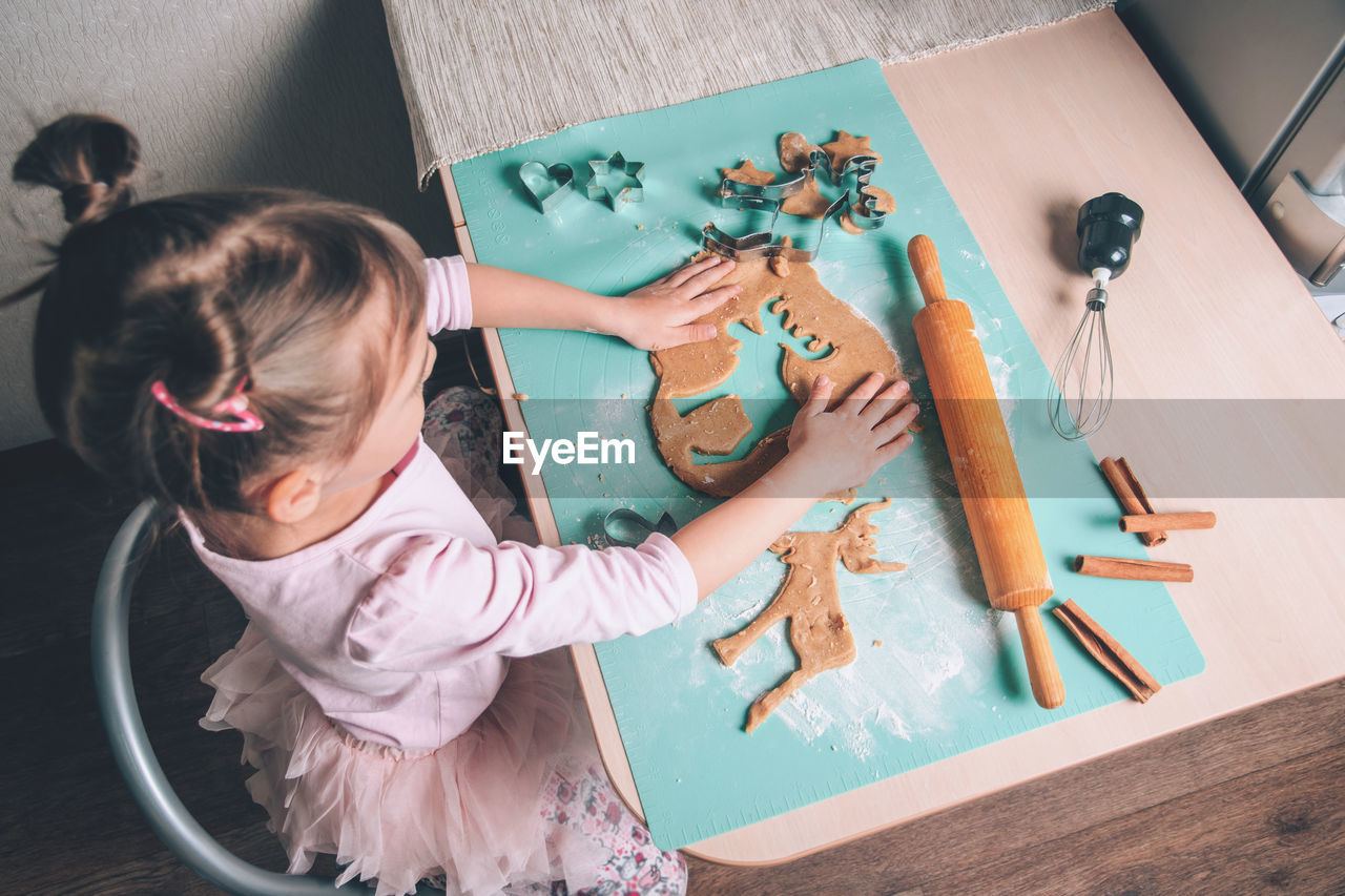 High angle view of cute girl holding table at home