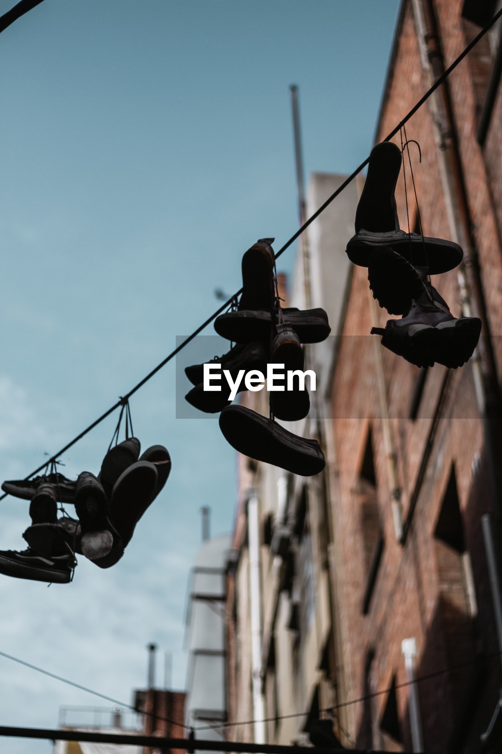 LOW ANGLE VIEW OF SHOES AGAINST THE SKY