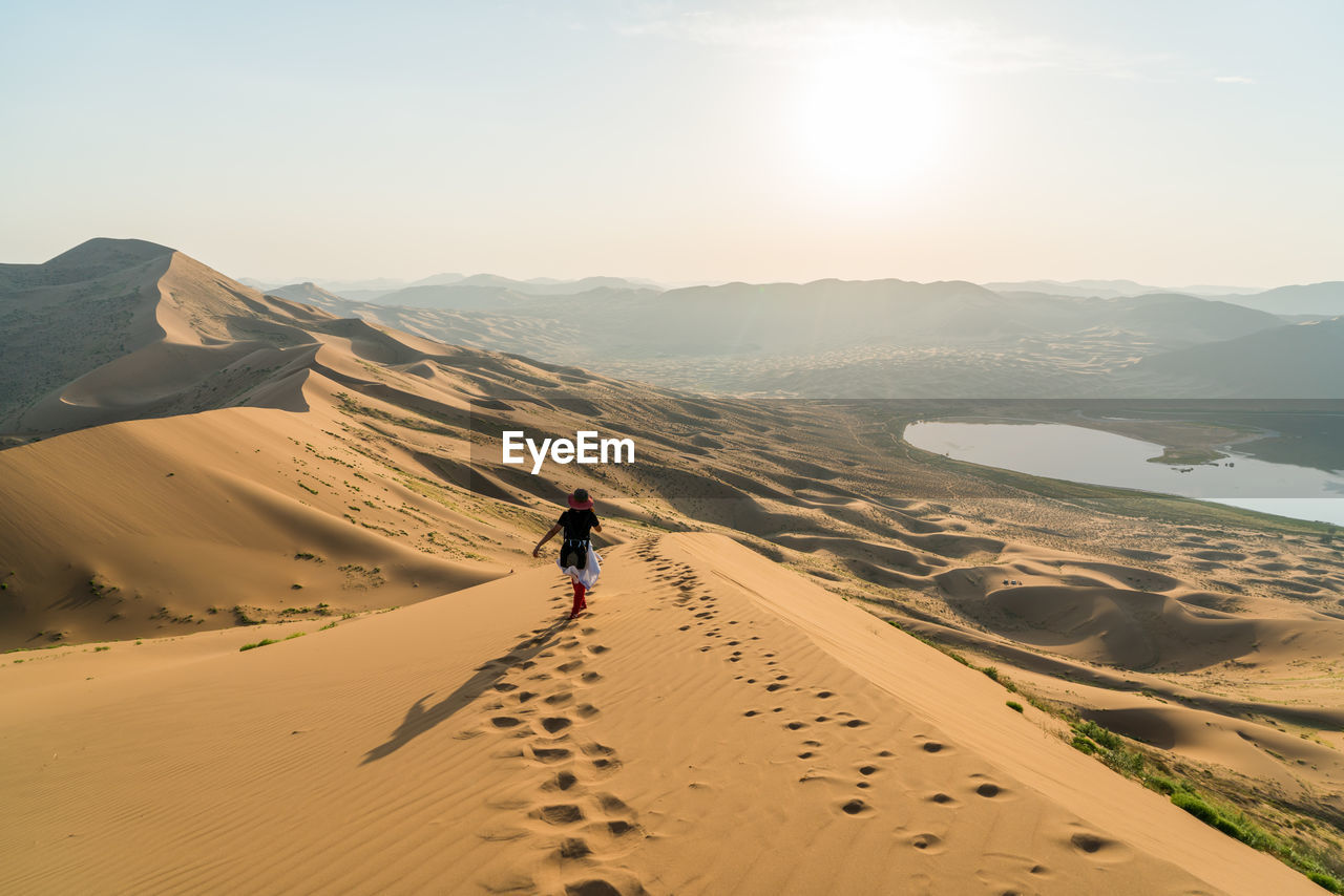 Rear View Of Woman Walking On Sand Dune In Badain Jaran Desert