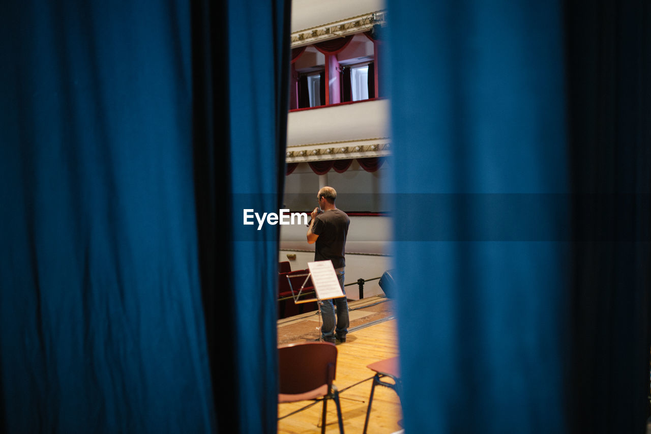 Rear View Of Man Standing On Stage Seen Through Curtain