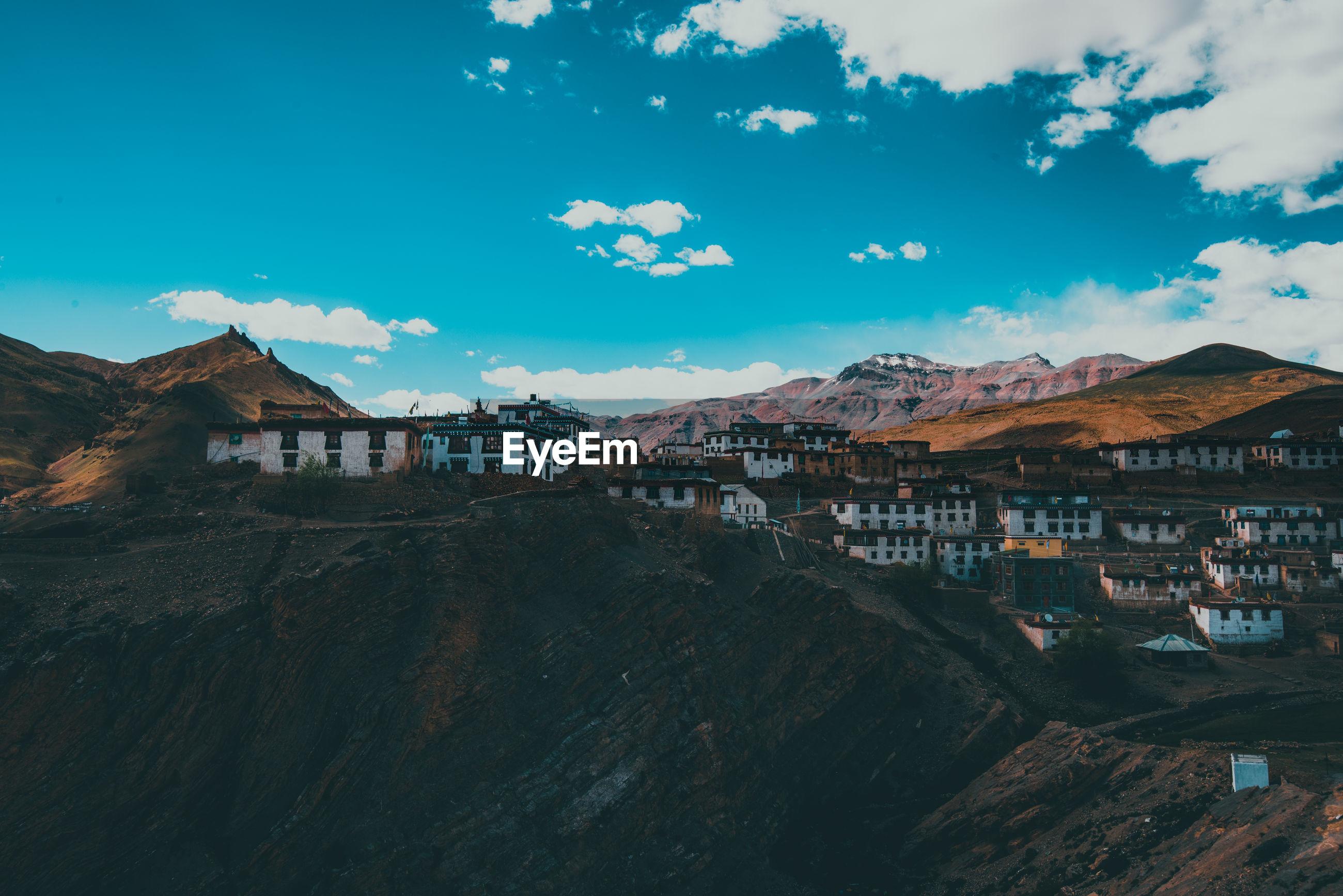 Houses on mountain against blue sky