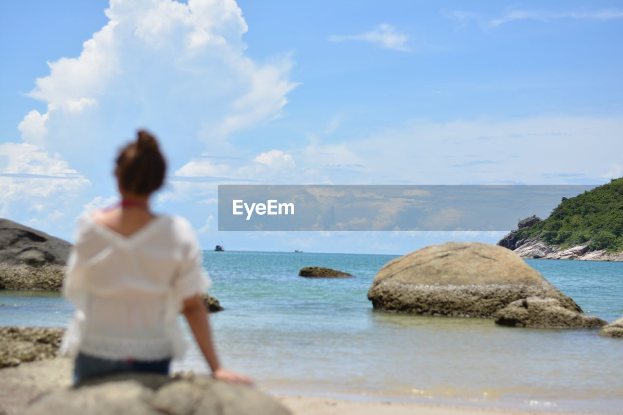 water, sea, sky, real people, one person, leisure activity, lifestyles, land, beach, cloud - sky, women, nature, scenics - nature, adult, beauty in nature, rear view, day, solid, outdoors, looking at view, contemplation