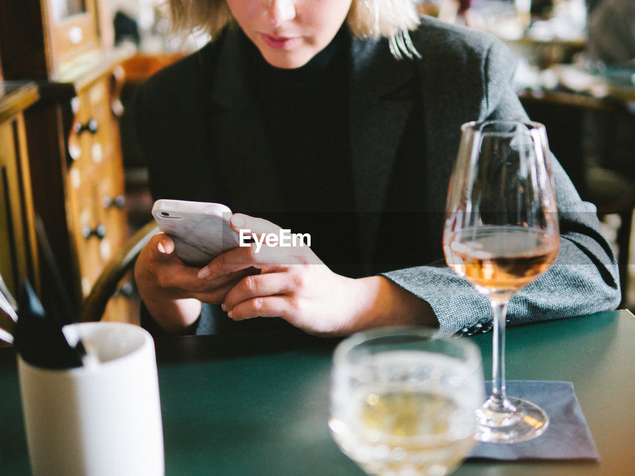 Midsection of woman using phone in restaurant
