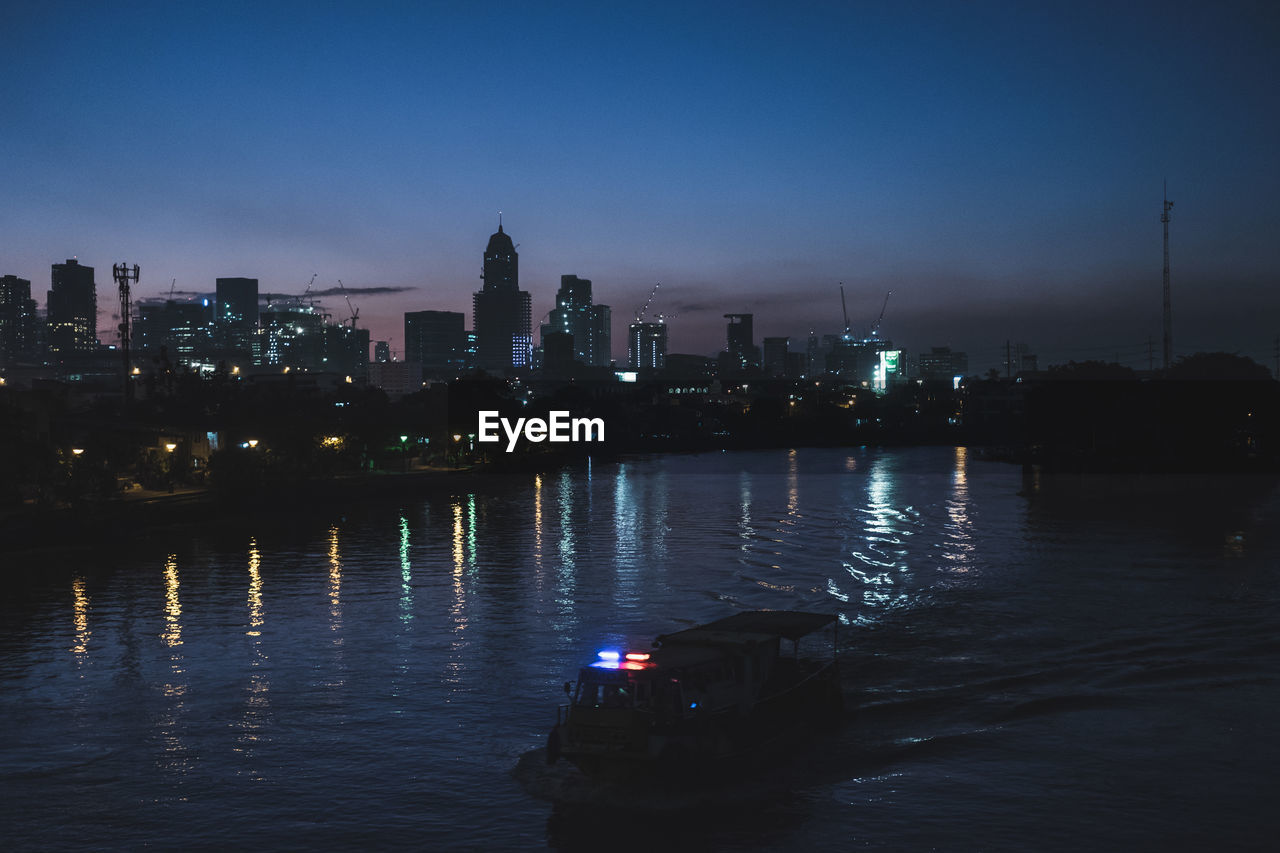 architecture, building exterior, water, modern, skyscraper, built structure, city, illuminated, sky, river, travel destinations, reflection, outdoors, transportation, night, cityscape, sunset, urban skyline, camera - photographic equipment, technology, nature, no people