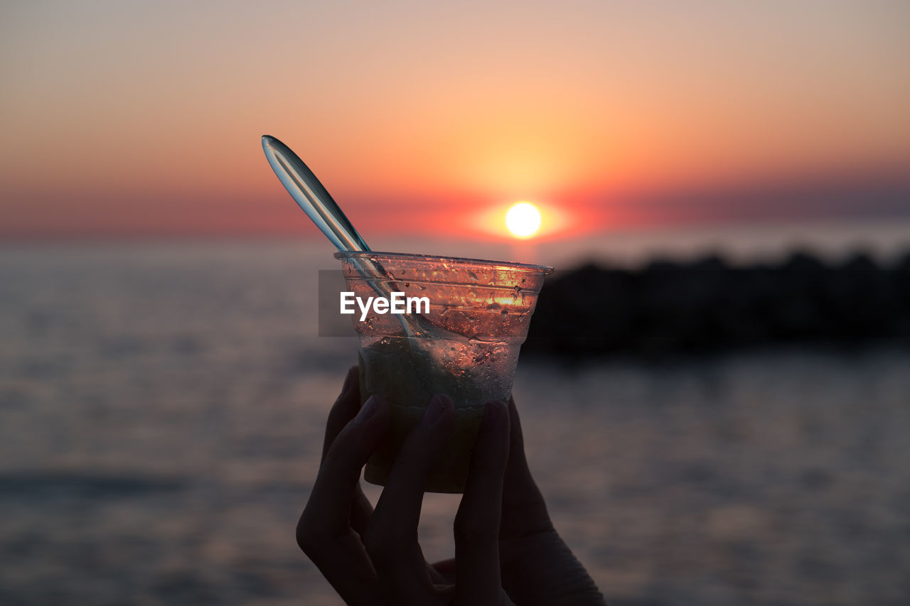 sunset, sky, water, sea, drink, refreshment, food and drink, beach, human hand, horizon over water, hand, orange color, nature, land, horizon, scenics - nature, straw, focus on foreground, beauty in nature, glass, sun, outdoors, cocktail