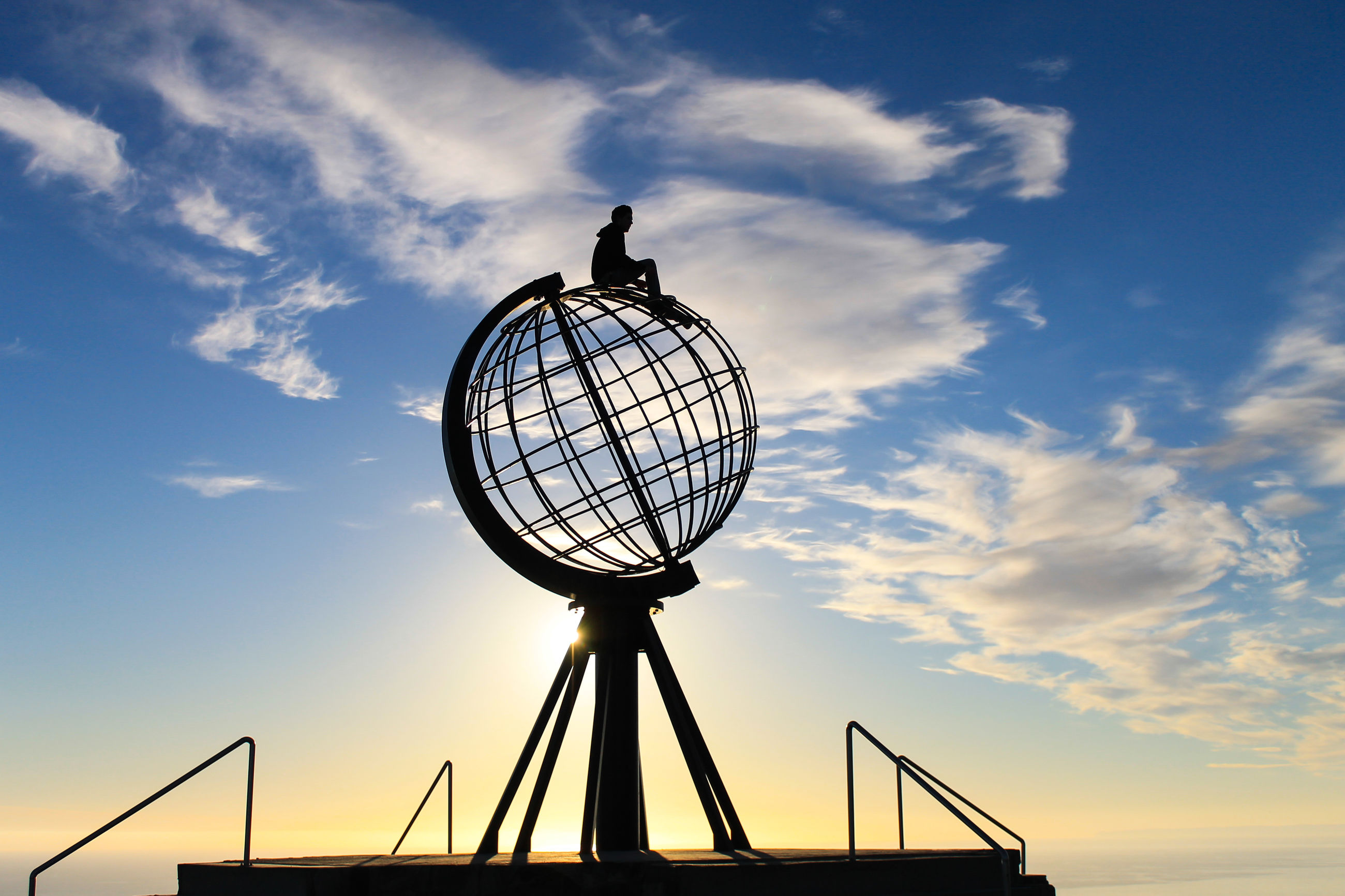 Low angle view of silhouette person sitting on metallic globe against sky during sunset