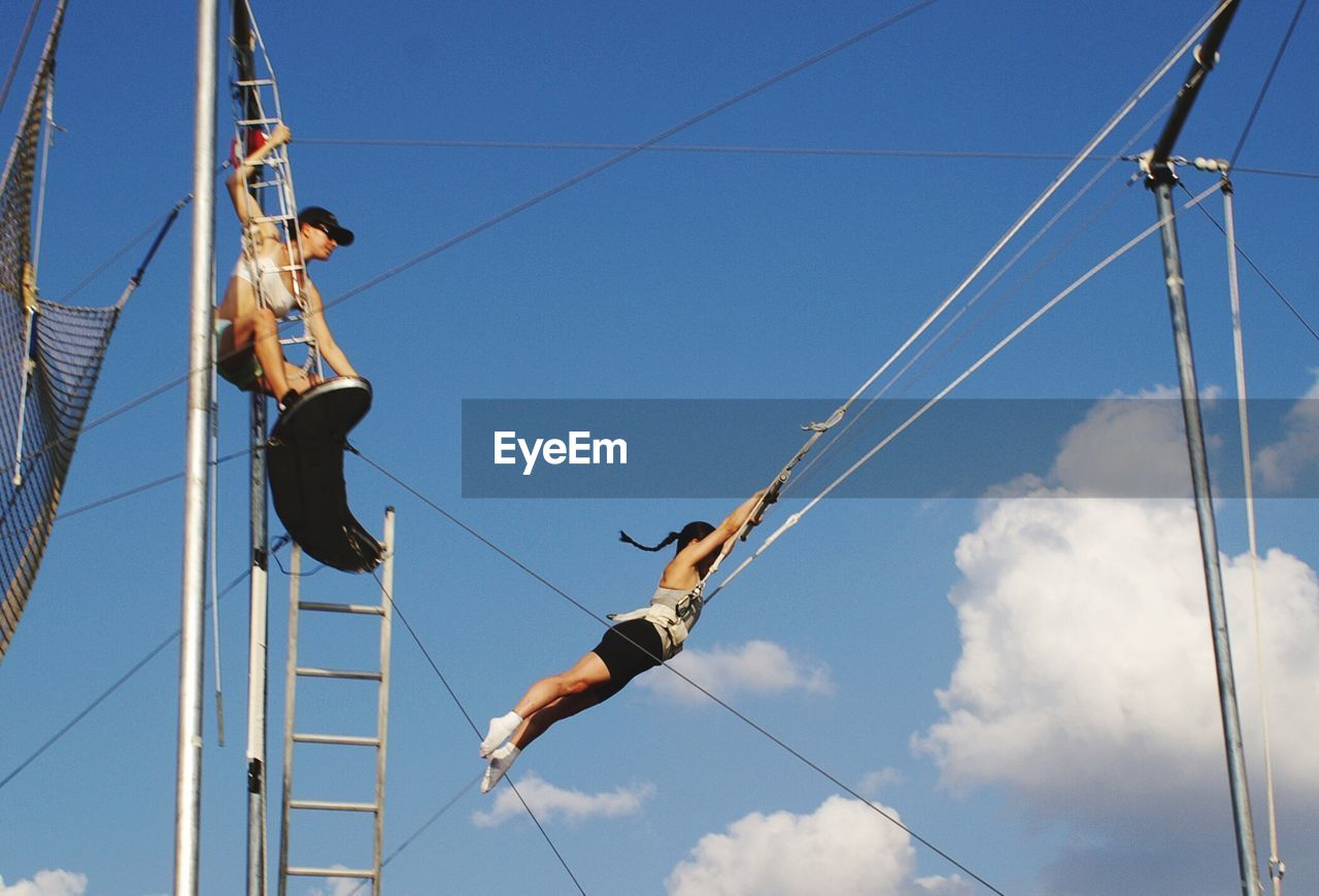 low angle view, sky, real people, day, rope, blue, outdoors, men, leisure activity, hanging, cable, lifestyles, risk, sunlight, sport, adventure, skill, climbing, one person, extreme sports, nature, people