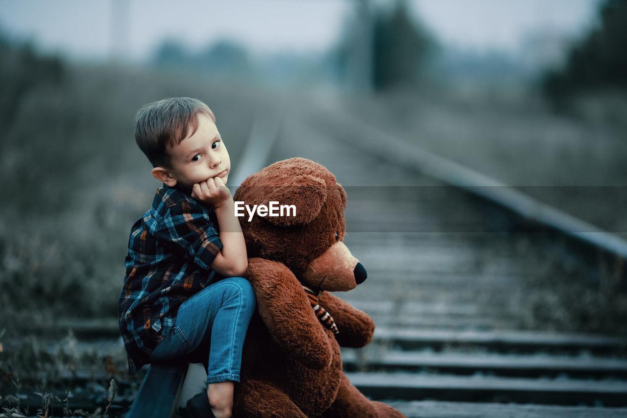 Boy with teddy bear sitting on railroad track