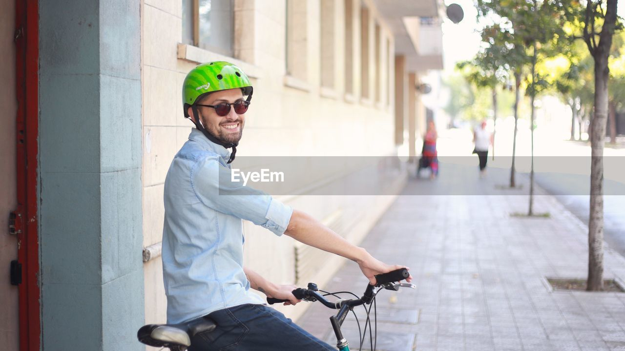 lifestyles, real people, smiling, helmet, casual clothing, focus on foreground, men, one person, transportation, bicycle, day, side view, portrait, young men, headwear, architecture, activity, three quarter length, sport, outdoors, riding
