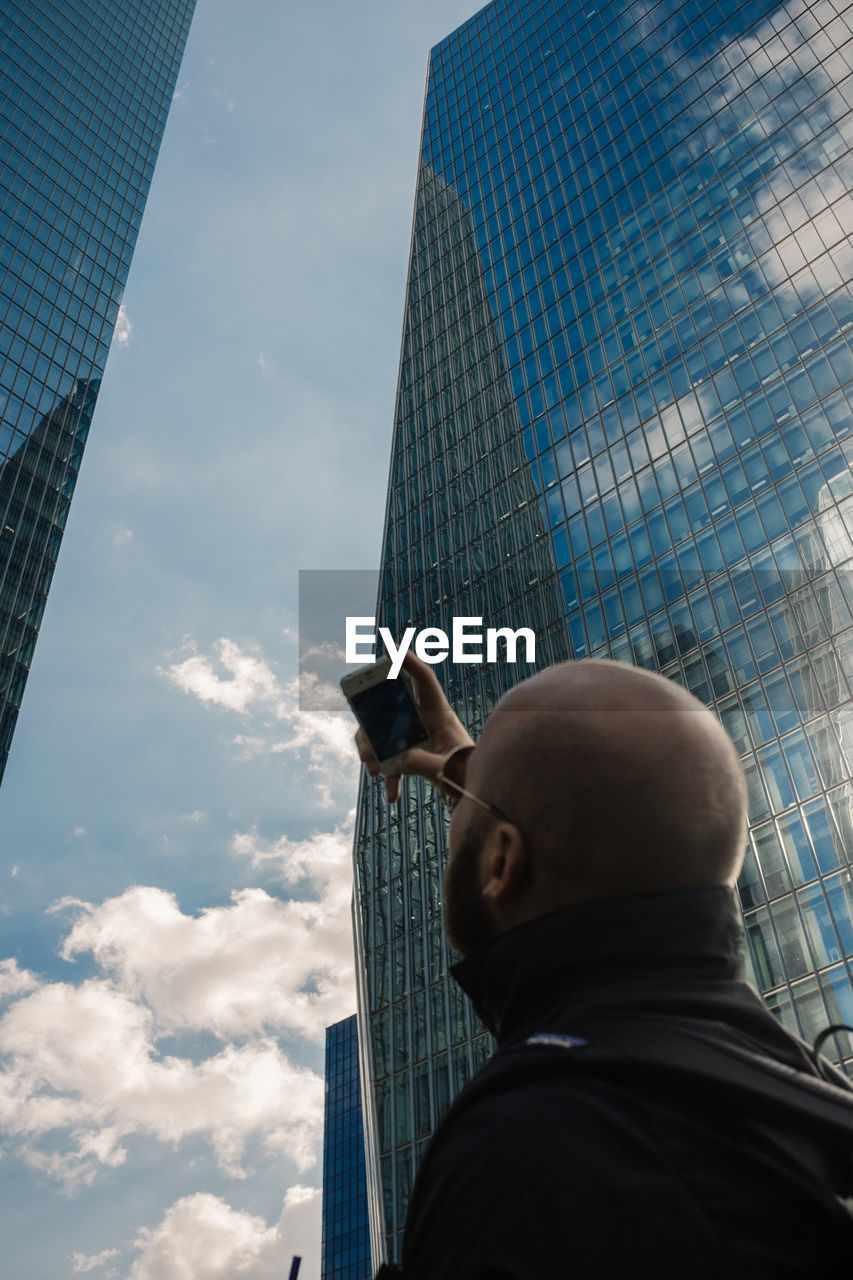architecture, built structure, building exterior, low angle view, building, city, sky, office building exterior, real people, one person, men, skyscraper, office, cloud - sky, tall - high, nature, day, headshot, modern, outdoors, financial district