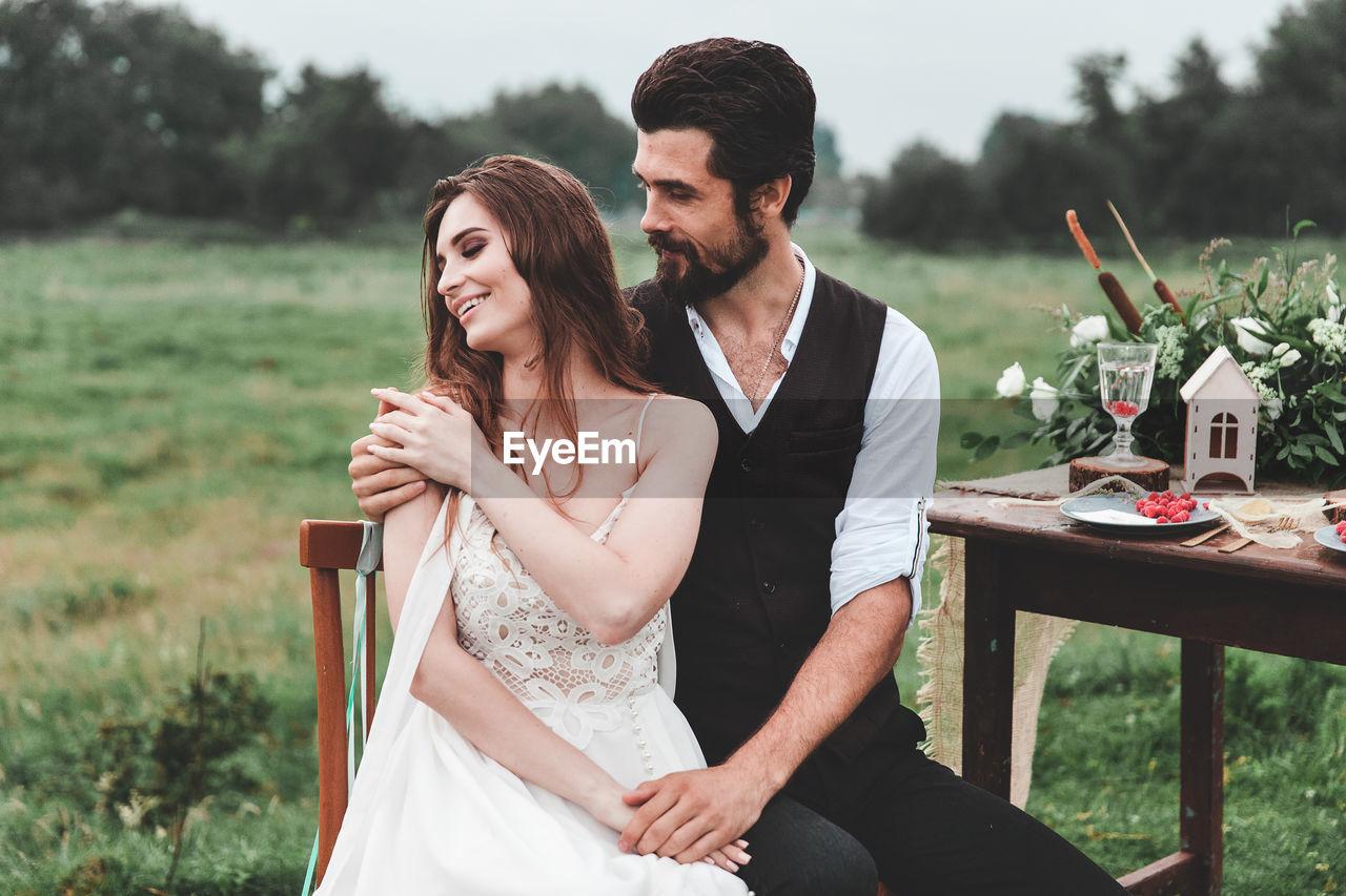 Happy Wedding Couple Sitting On Chair At Farm