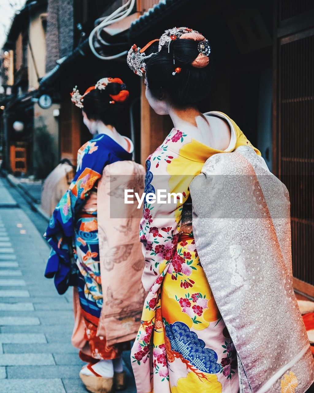 real people, rear view, traditional clothing, outdoors, kimono, leisure activity, two people, day, multi colored, building exterior, lifestyles, built structure, women, togetherness, architecture, city, adult, people