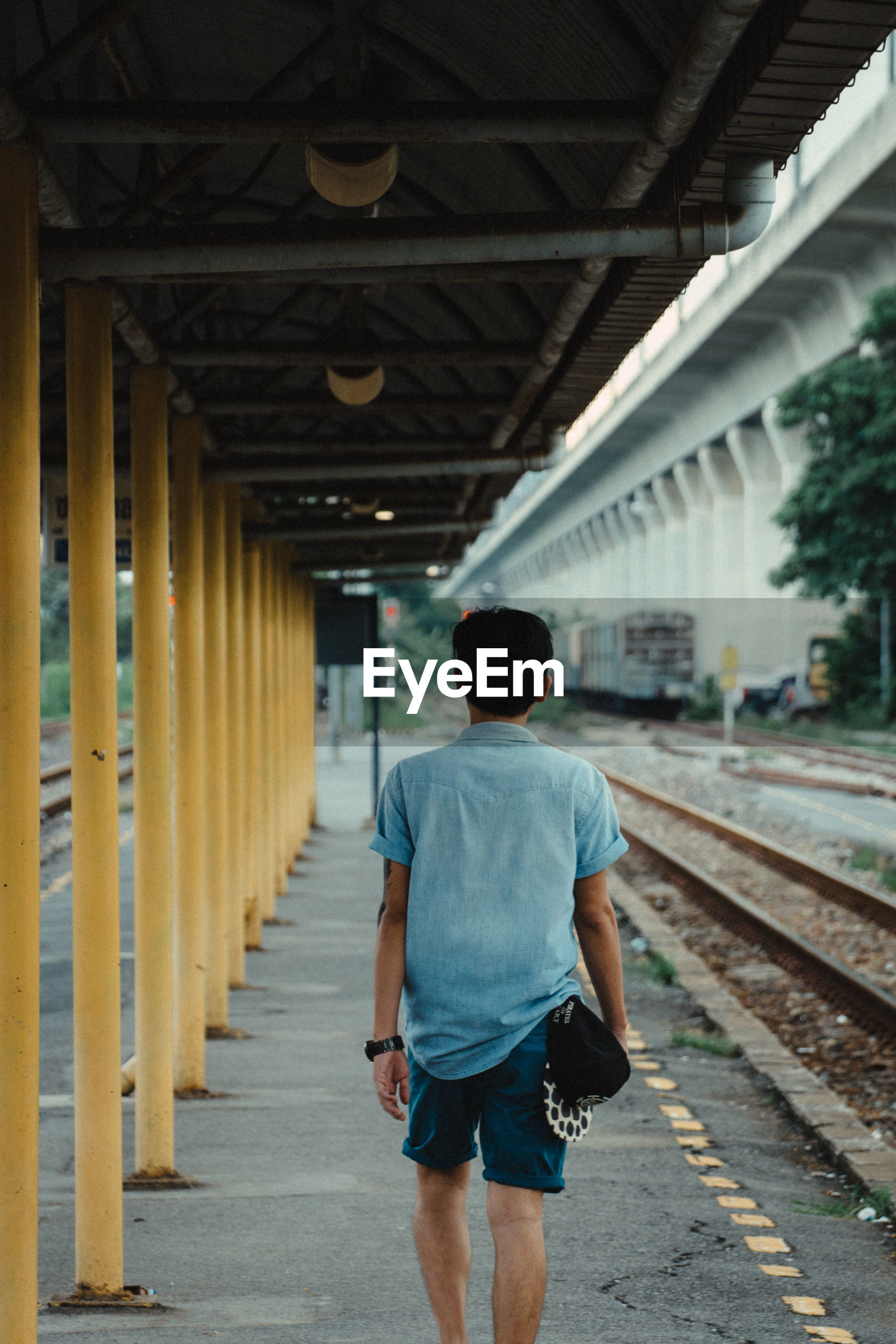 rear view, architecture, one person, transportation, built structure, real people, casual clothing, men, the way forward, direction, bridge, rail transportation, day, bridge - man made structure, railroad track, lifestyles, walking, track, diminishing perspective, outdoors, architectural column, shorts