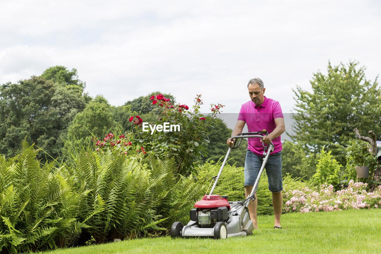 FULL LENGTH OF MAN STANDING ON GRASS AGAINST PLANTS