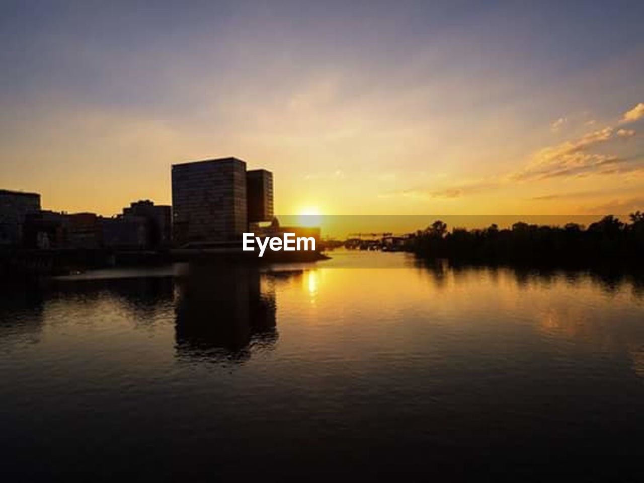 sunset, reflection, architecture, built structure, sky, building exterior, water, city, waterfront, silhouette, outdoors, cloud - sky, skyscraper, no people, urban skyline, nature, tree, modern, beauty in nature, cityscape, day